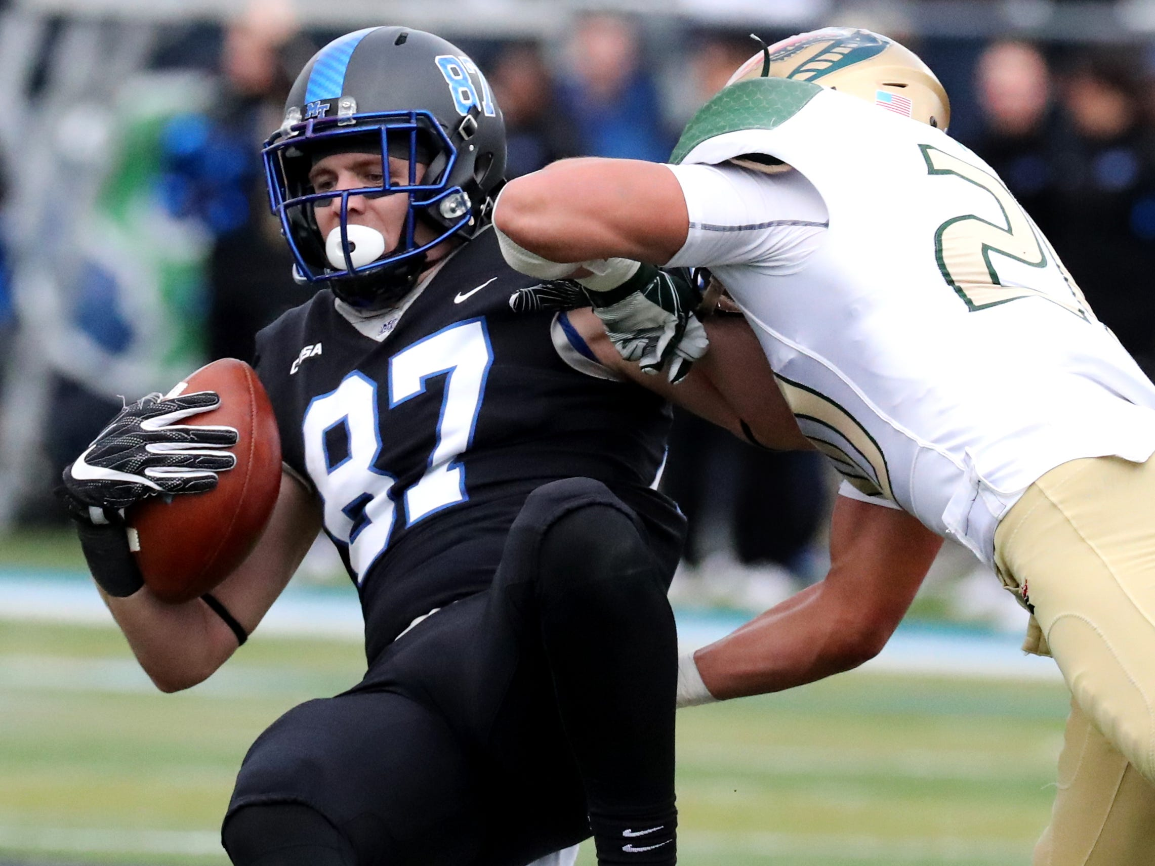 MTSU's wide receiver Gatlin Casey (87) catches the ball and runs as UAB's linebacker Kristopher Moll (20)makes the  tackle during the Conference USA Championship at MTSU on Saturday, Dec. 1, 2018.