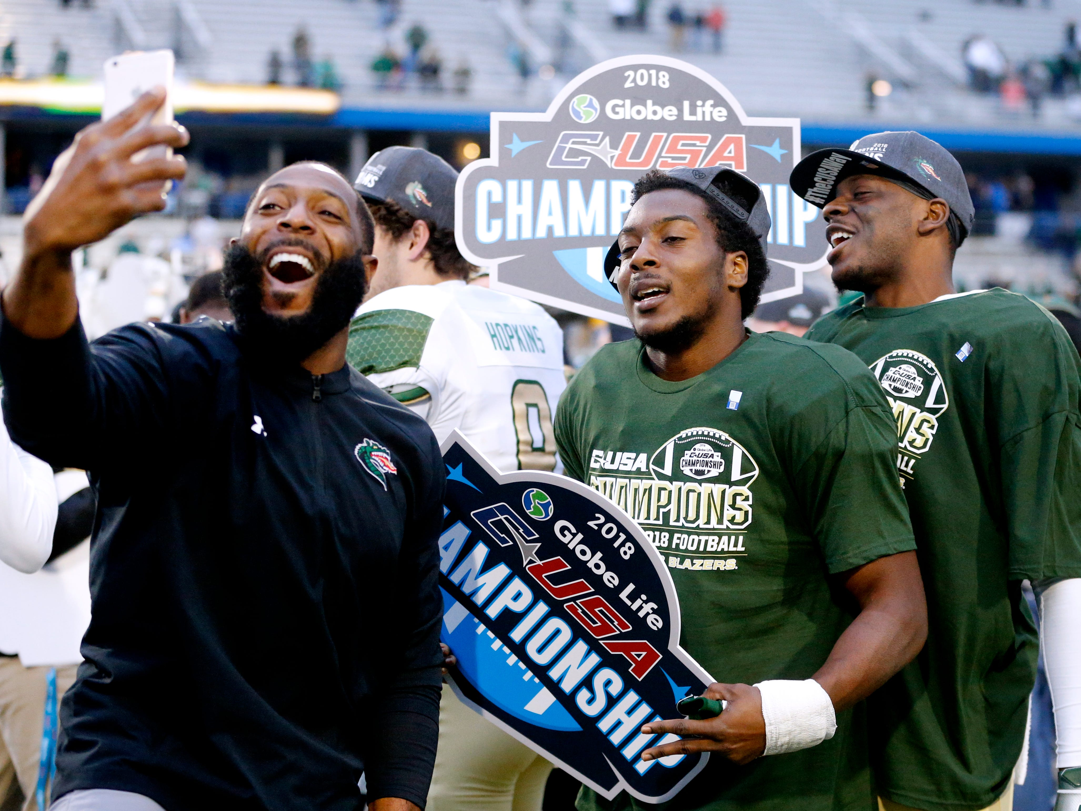 UAB assistant coach, UAB's running back Spencer Brown (28), and UAB's wide receiver Kendall Parham (16) celebrate the 27-25 win over MTSU in the Conference USA Championship at MTSU on Saturday, Dec. 1, 2018.