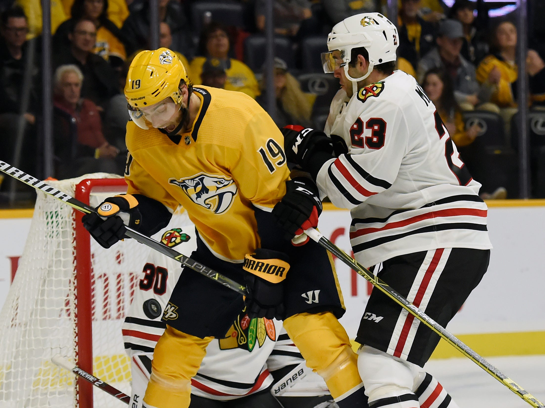 Nashville Predators center Calle Jarnkrok (19) of Sweden, and Chicago Blackhawks defenseman Brandon Manning (23) battle for the puck during the second period of an NHL hockey game Saturday, Dec. 1, 2018, in Nashville, Tenn.