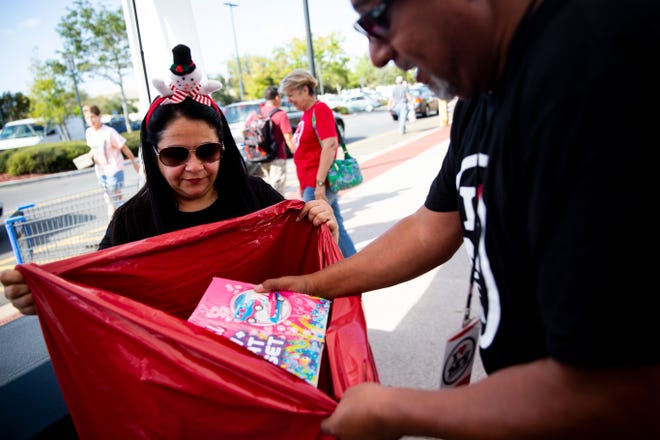 Tina Hernandez-Stewart, left, and Levin Stewart pack donated toys into a plastic bag during the Mission Christmas toy drive organized by Living Word Family Church and The Salvation Army on Sunday, Dec. 2, 2018, at Walmart at I-75 and Immokalee Road in North Naples.
