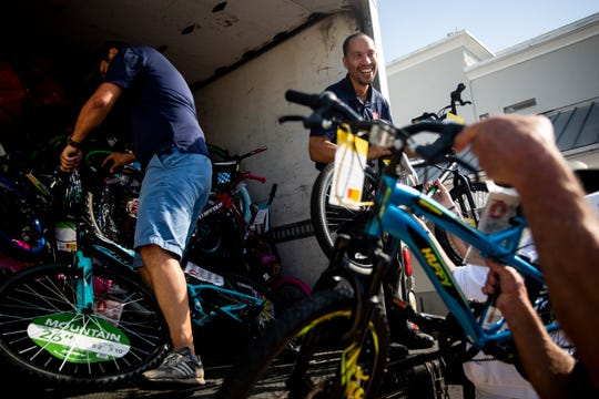 David Rojas, from left, Joey Tejada and Joe Milan load donated bikes onto a truck during the Mission Christmas toy drive organized by Living Word Family Church and The Salvation Army on Sunday, Dec. 2, 2018, at Walmart at I-75 and Immokalee Road in North Naples.