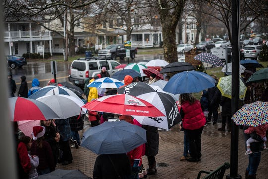 Kids and parents await their opportunity to see Santa despite persistent rain resulting in a sea of umbrellas during Saturday's Christmas Candlelight Walking Tour.