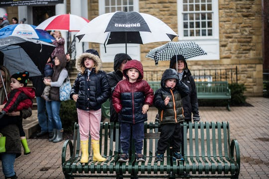 Umbrellas and hoods were up as families awaited Santa's rainy arrival in front of the Granville Public Library Saturday.