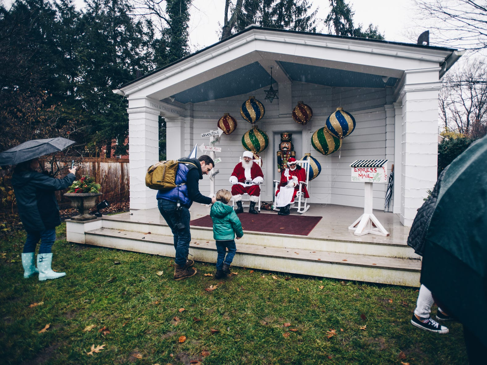 Kids and parents enjoy their opportunity to see Santa despite persistent rain during Saturday's Christmas Candlelight Walking Tour.