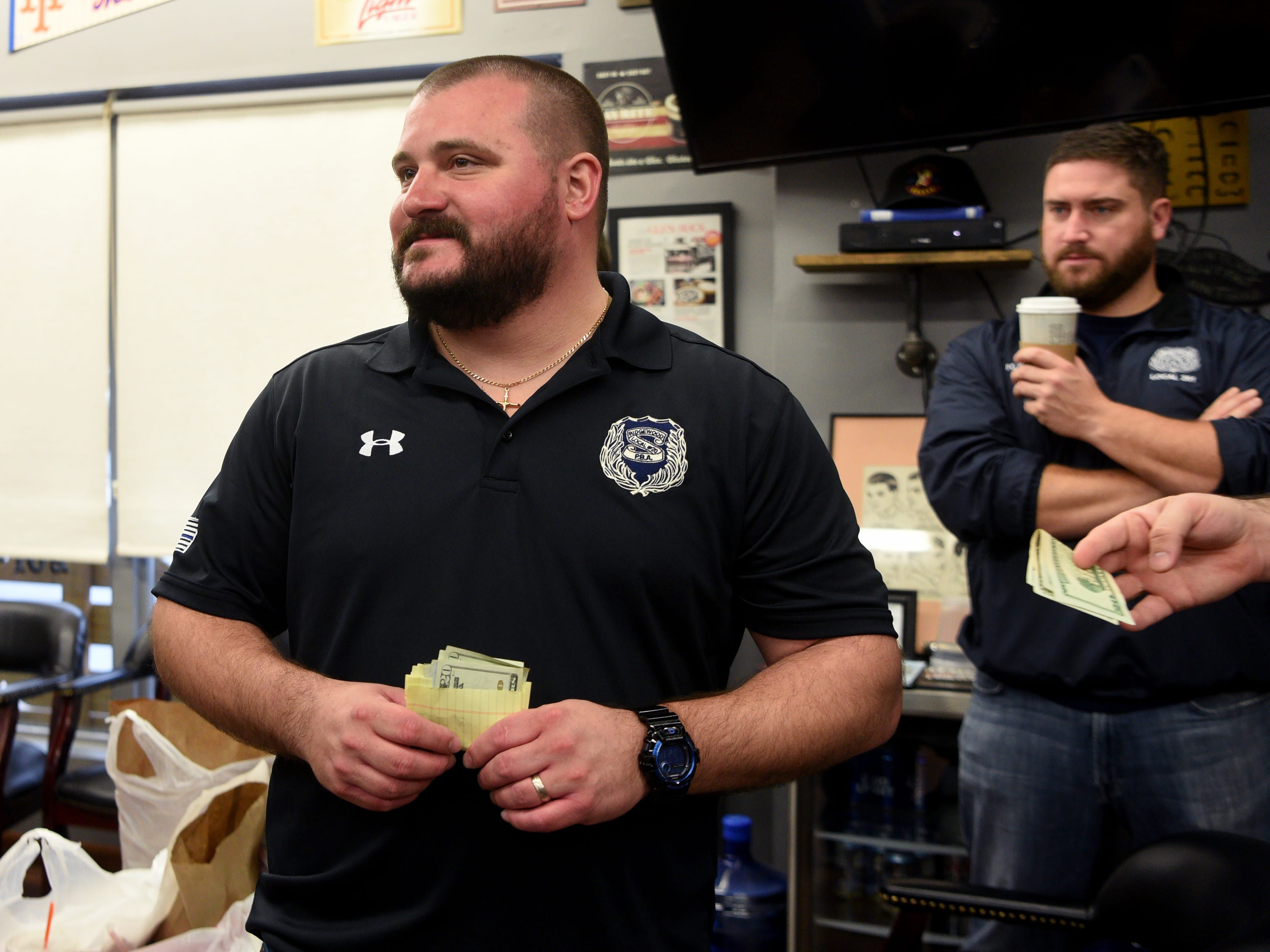 """Ridgewood police Patrolman Sean Amoruso, chairman of the """"Shave-Off,"""" collects money for the event. The Ridgewood, Wyckoff and Franklin Lakes PBAs held their No-Shave November Annual Shave-Off at Iconic Barber Shop in Glen Rock on Sunday, December 2, 2018. The money raised will help a Ridgewood family pay medical bills. Iconic Barber Shop also donated 100% percent of the proceeds from Sunday morning's Shave-Off."""