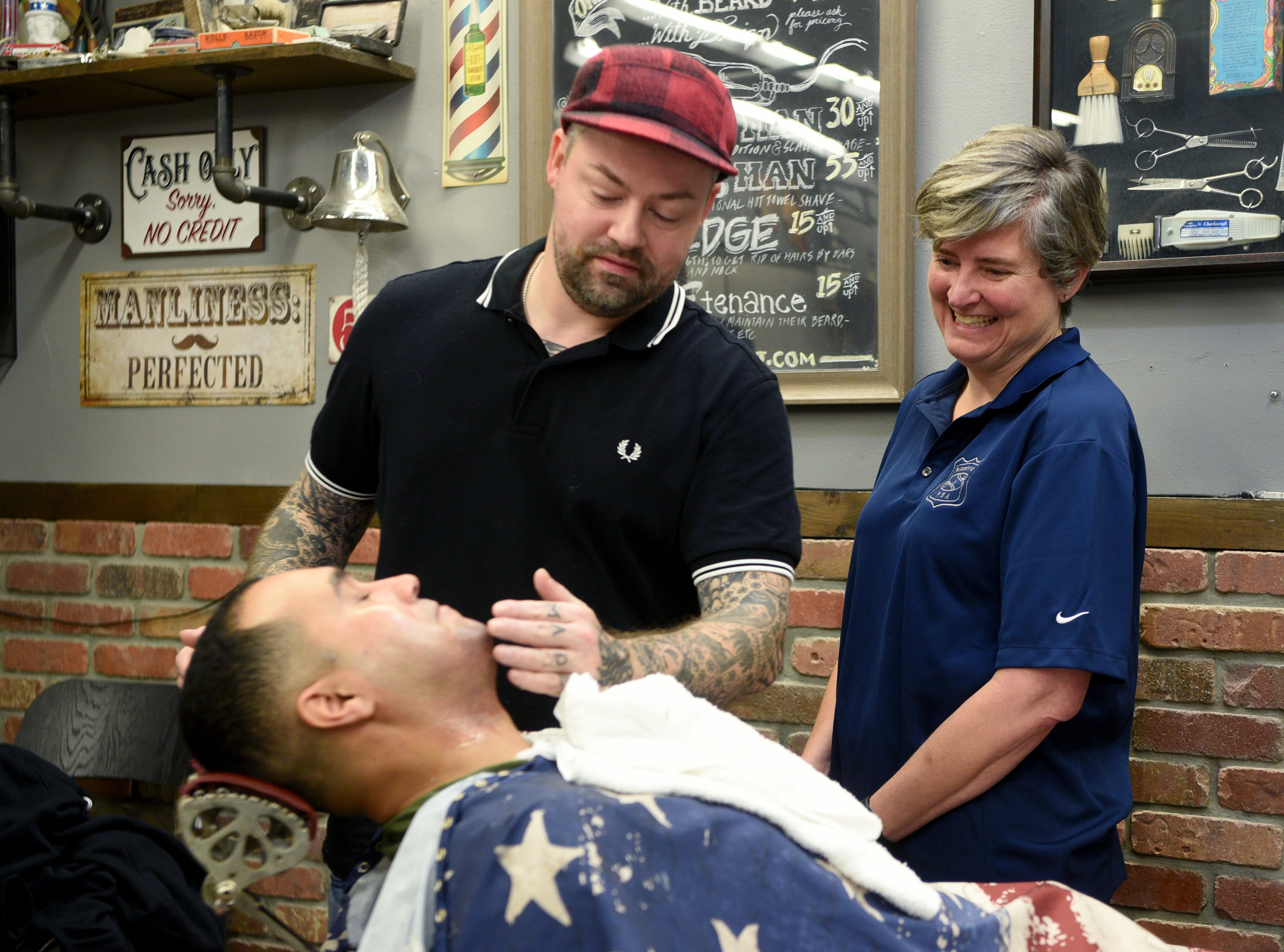 Ridgewood Police Chief Jacqueline Luthcke watches while Patrolman Hector Perez is shaved by Shea Flynn. The Ridgewood, Wyckoff and Franklin Lakes PBAs held their No-Shave November Annual Shave-Off at Iconic Barber Shop in Glen Rock on Sunday, December 2, 2018. The money raised will help a Ridgewood family pay medical bills. Iconic Barber Shop also donated 100% percent of the proceeds from Sunday morning's Shave-Off.