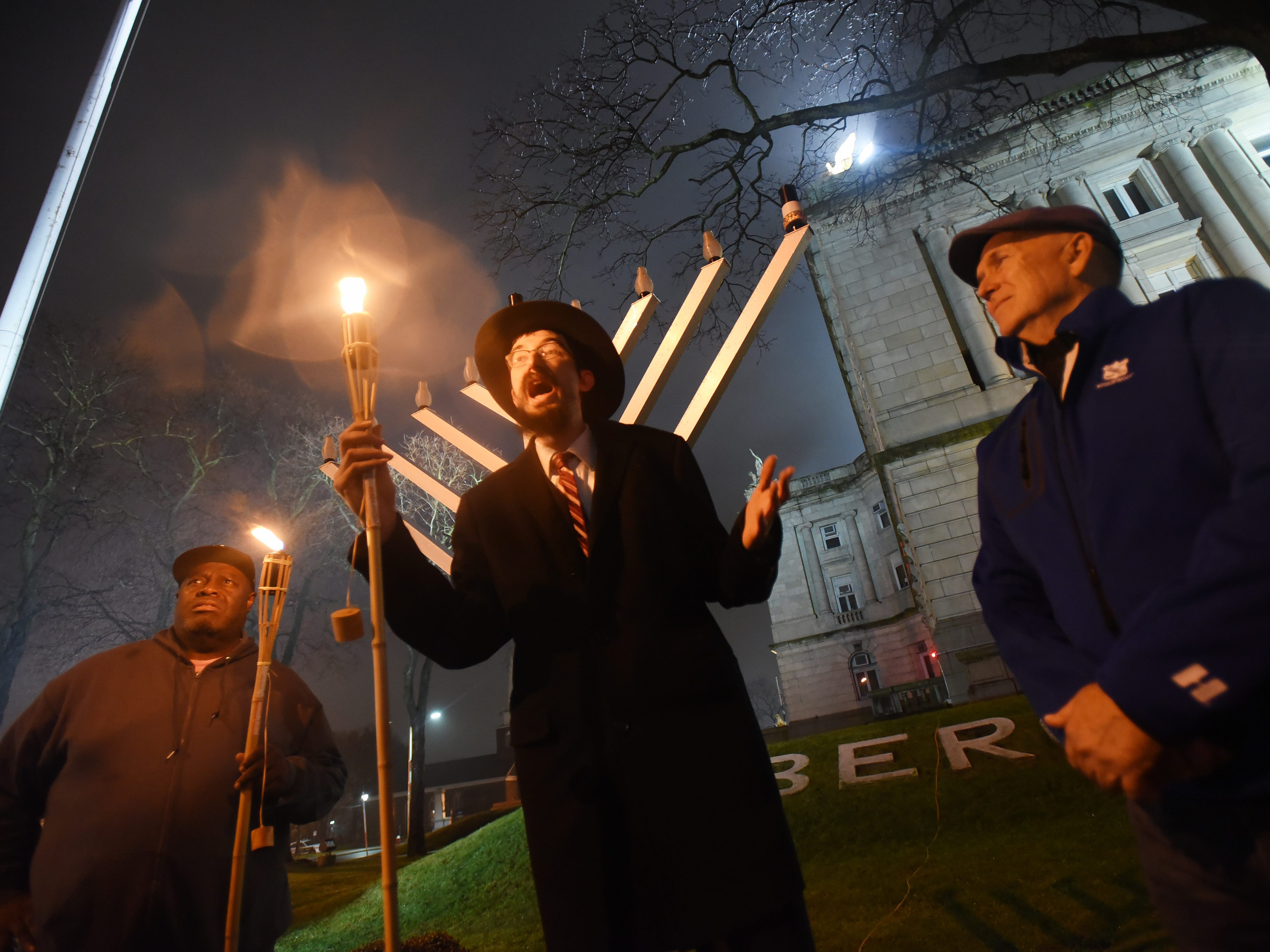 Rabbi Mendy Kaminker from Chabad of Hackensack, holds a torch as he speaks to participants while Deputy Hackensack Mayor David Sims (L) and Hackensack Mayor John Labrosse (R) look on prior to the lighting ceremony to celebrate the 2018 Hanukkah season at the front lawn of Bergen County Courthouse in Hackensack on 12/02/18.