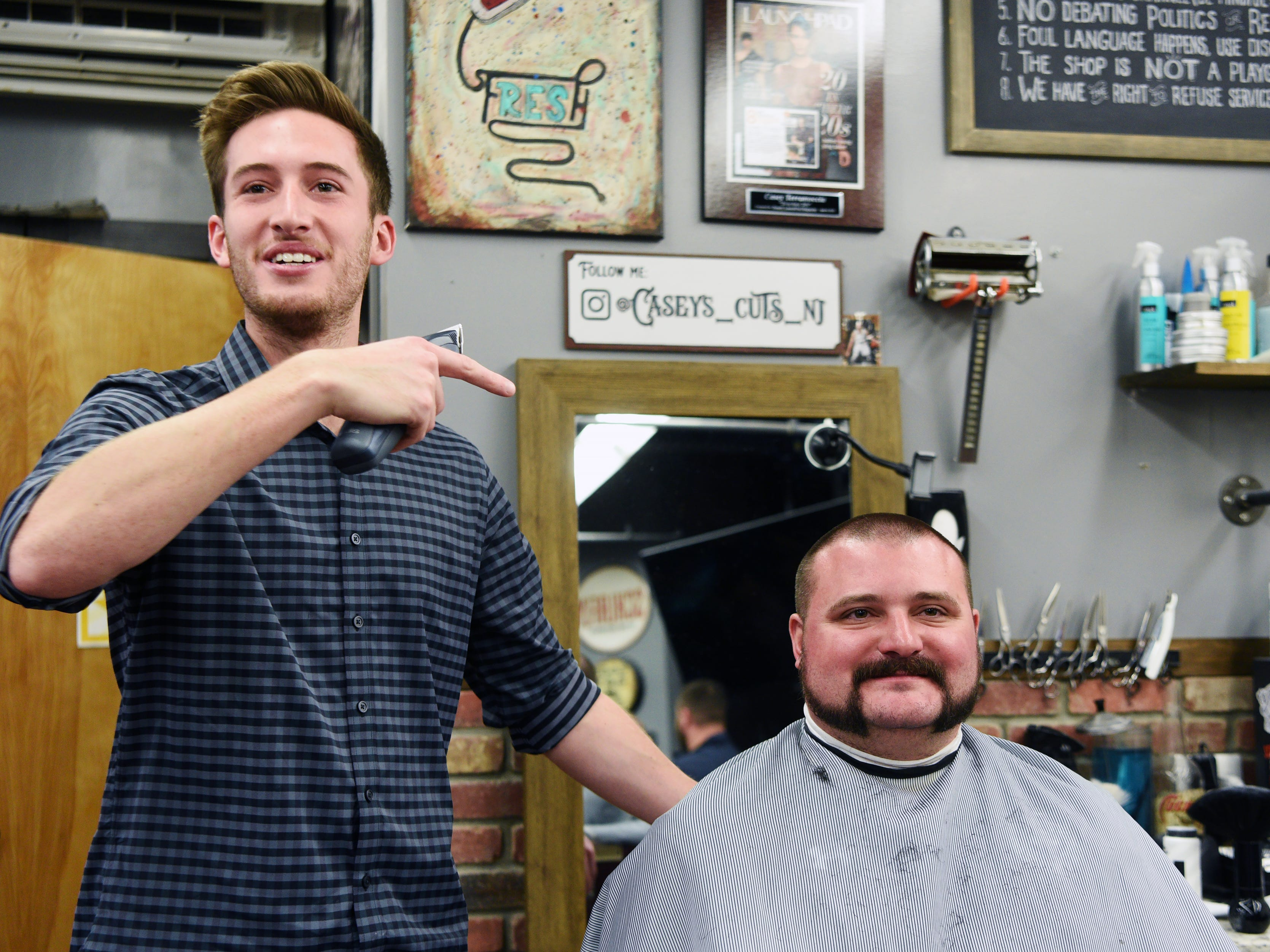 Casey Terramoccia, owner of Iconic Barber Shop, jokingly shaved off a portion of Patrolman Sean Amoruso's beard during the Shave-Off. The Ridgewood, Wyckoff and Franklin Lakes PBAs held their No-Shave November Annual Shave-Off at Iconic Barber Shop in Glen Rock on Sunday, December 2, 2018. The money raised will help a Ridgewood family pay medical bills. Iconic Barber Shop also donated 100% percent of the proceeds from Sunday morning's Shave-Off.