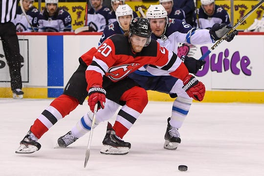 Dec 1, 2018; Newark, NJ, USA; New Jersey Devils center Blake Coleman (20) and Winnipeg Jets defenseman Cameron Schilling (6) battle for a loose puck during the first period at Prudential Center.