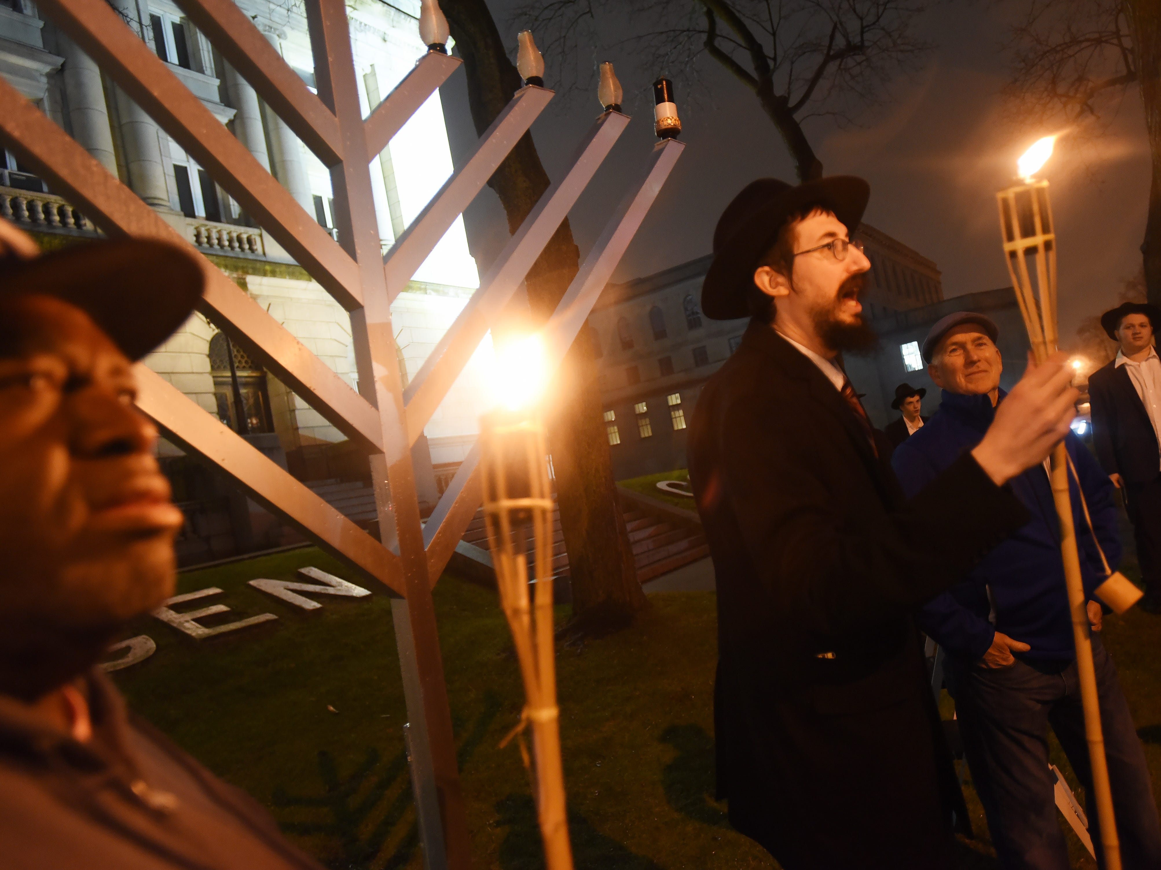 Rabbi Mendy Kaminker from Chabad of Hackensack, holds a torch as he speaks to participants while Deputy Hackensack Mayor David Sims (foreground) looks on prior to the lighting ceremony to celebrate the 2018 Hanukkah season at the front lawn of Bergen County Courthouse in Hackensack on 12/02/18.