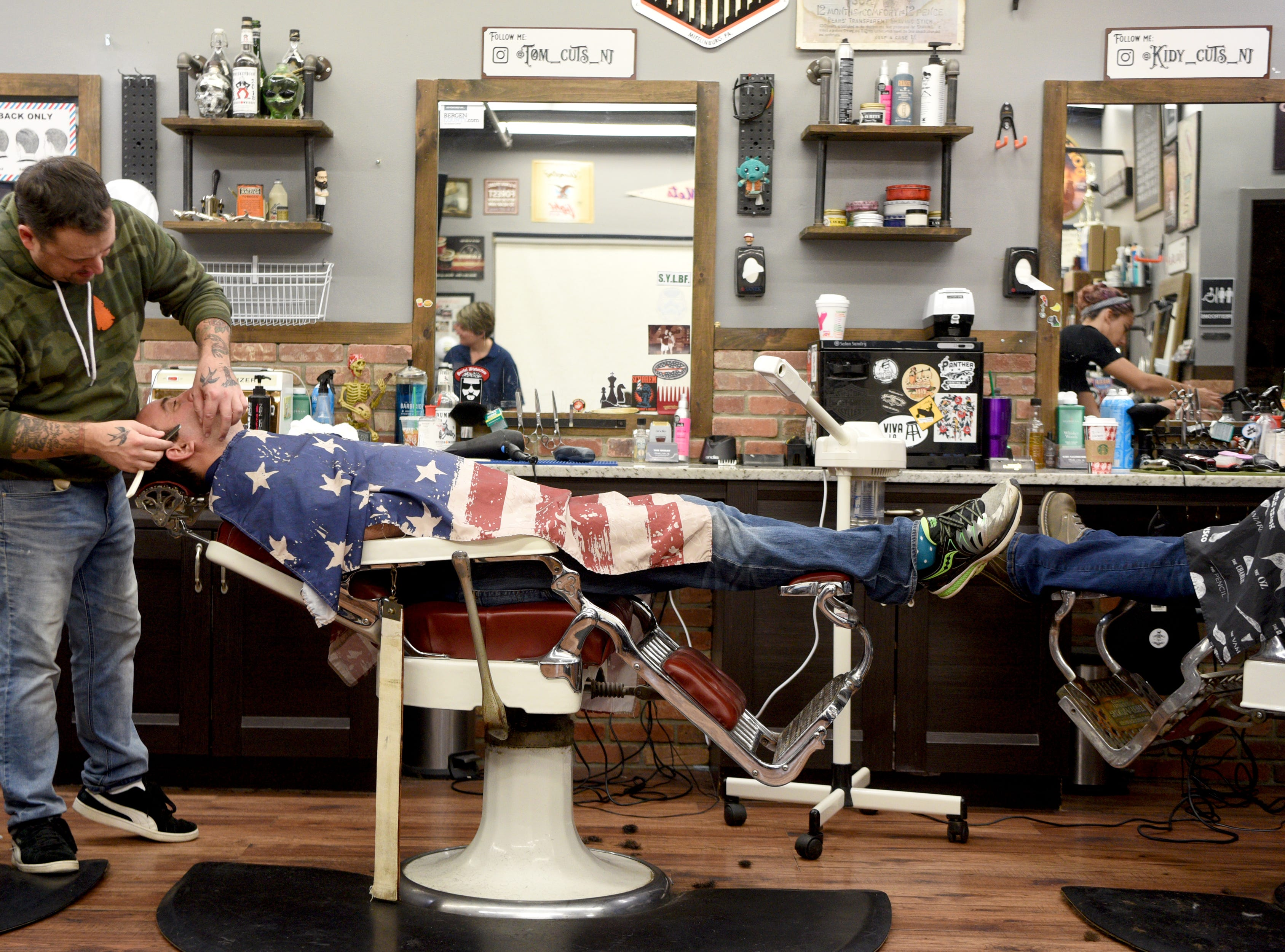 """Ridgewood police Sgt. Michael Lembo gets a shave from Tom Wright at Iconic Barbershop. The Ridgewood PBA, along with Wyckoff and Franklin Lakes' PBAs held there No-Shave November Annual Shave Off at Iconic Barbershop in Glen Ridge on Sunday, December 2, 2018. The money raised from help a Ridgewood family pay medical bills. Iconic Barbershop matching 100% percent of the proceeds from Sunday mornings """"Shave Off."""""""