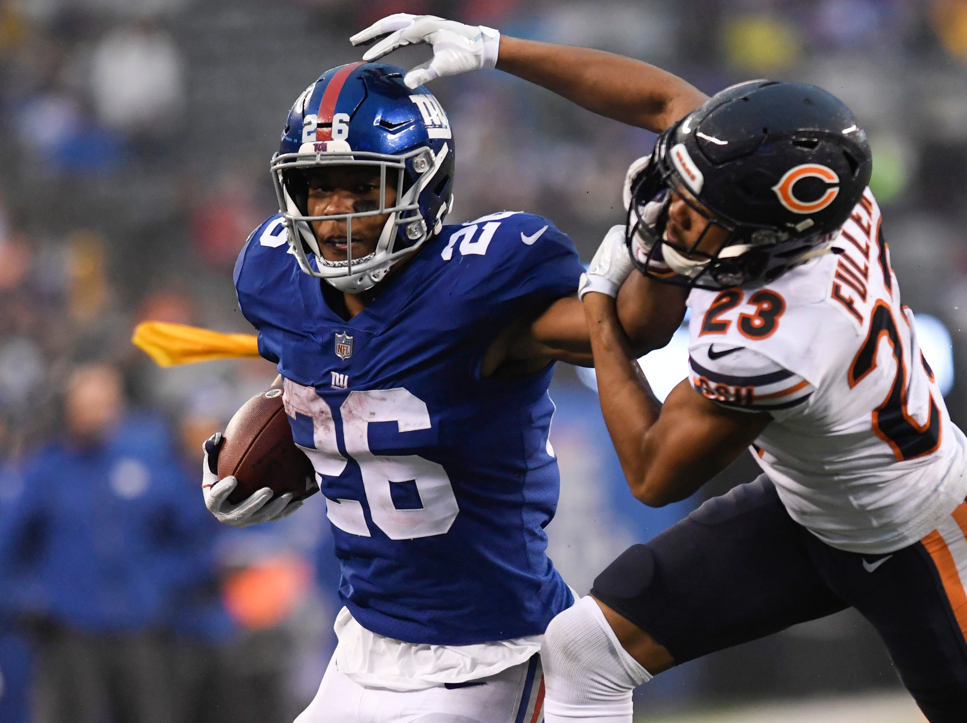 New York Giants running back Saquon Barkley (26) stiff-arms Chicago Bears cornerback Kyle Fuller (23) as a flag is thrown for a penalty against the Giants. The New York Giants defeat the Chicago Bears in overtime 30-27 on Sunday, Dec. 2, 2018, in East Rutherford.