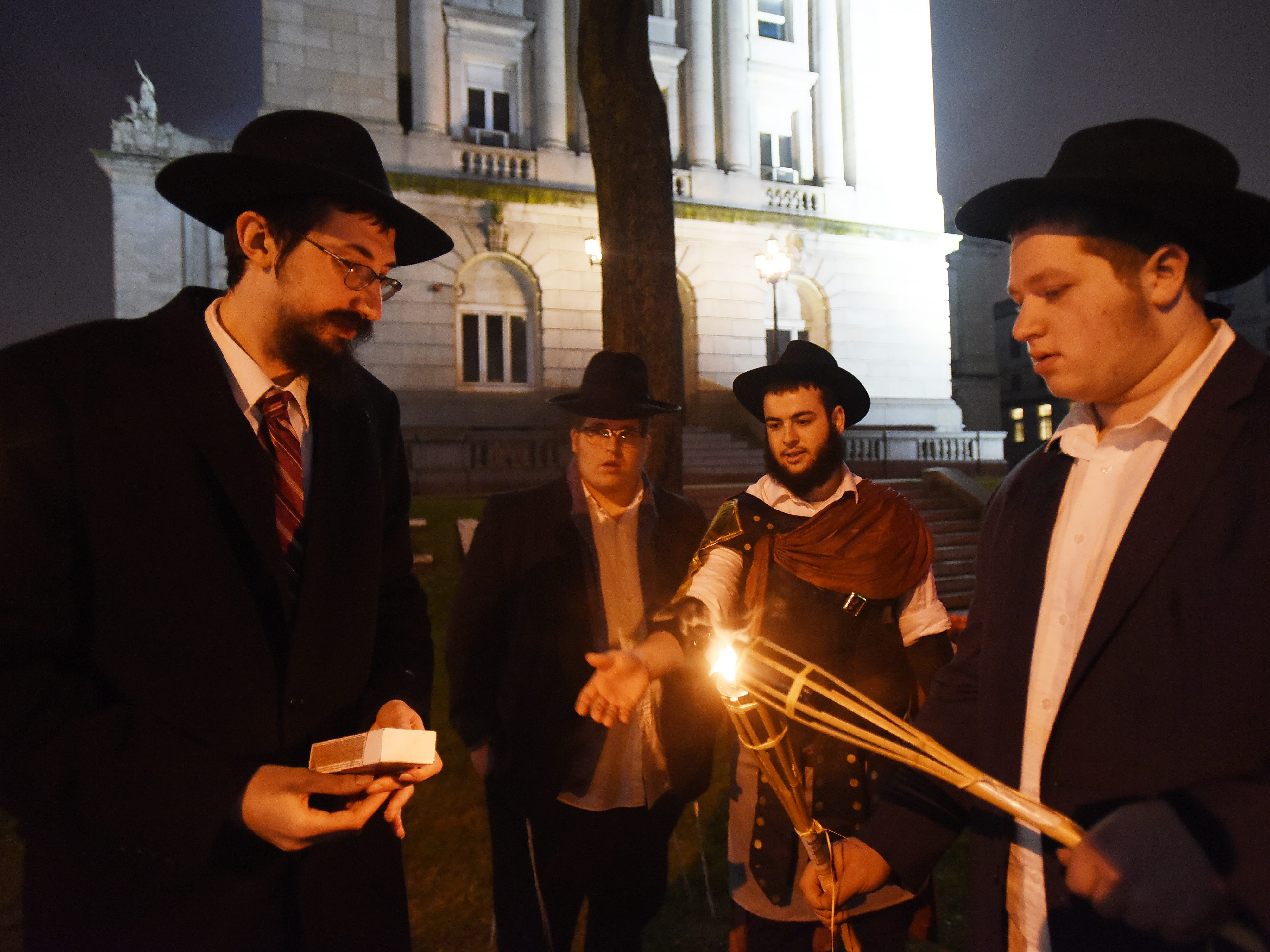 Members of Chabad of Hackensack, light a torch as Rabbi Mendy Kaminker (L) looks on prior the lighting ceremony to celebrate the 2018 Hanukkah season at the front lawn of Bergen County Courthouse in Hackensack on 12/02/18.