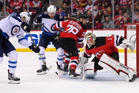 Dec 1, 2018; Newark, NJ, USA; Winnipeg Jets center Adam Lowry (17) attempts to put in a rebound and New Jersey Devils goaltender Keith Kinkaid (1) makes a save during the second period at Prudential Center.