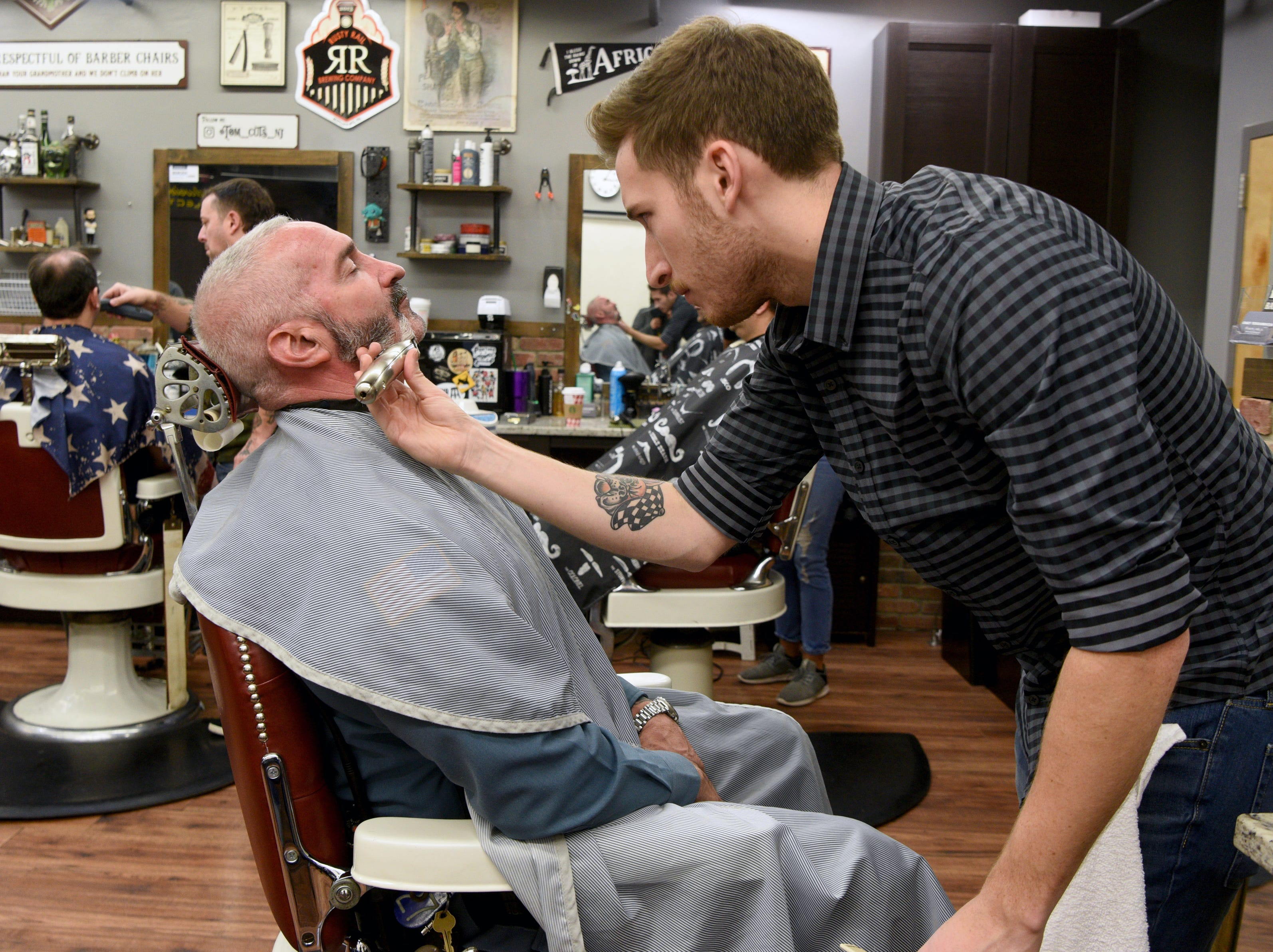 Ridgewood police Patrolman Patrick Elwood gets a shave from Casey Terramoccia, owner of Iconic Barber Shop. The Ridgewood, Wyckoff and Franklin Lakes PBAs held their No-Shave November Annual Shave-Off at Iconic Barber Shop in Glen Rock on Sunday, December 2, 2018. The money raised will help a Ridgewood family pay medical bills. Iconic Barber Shop also donated 100% percent of the proceeds from Sunday morning's Shave-Off.