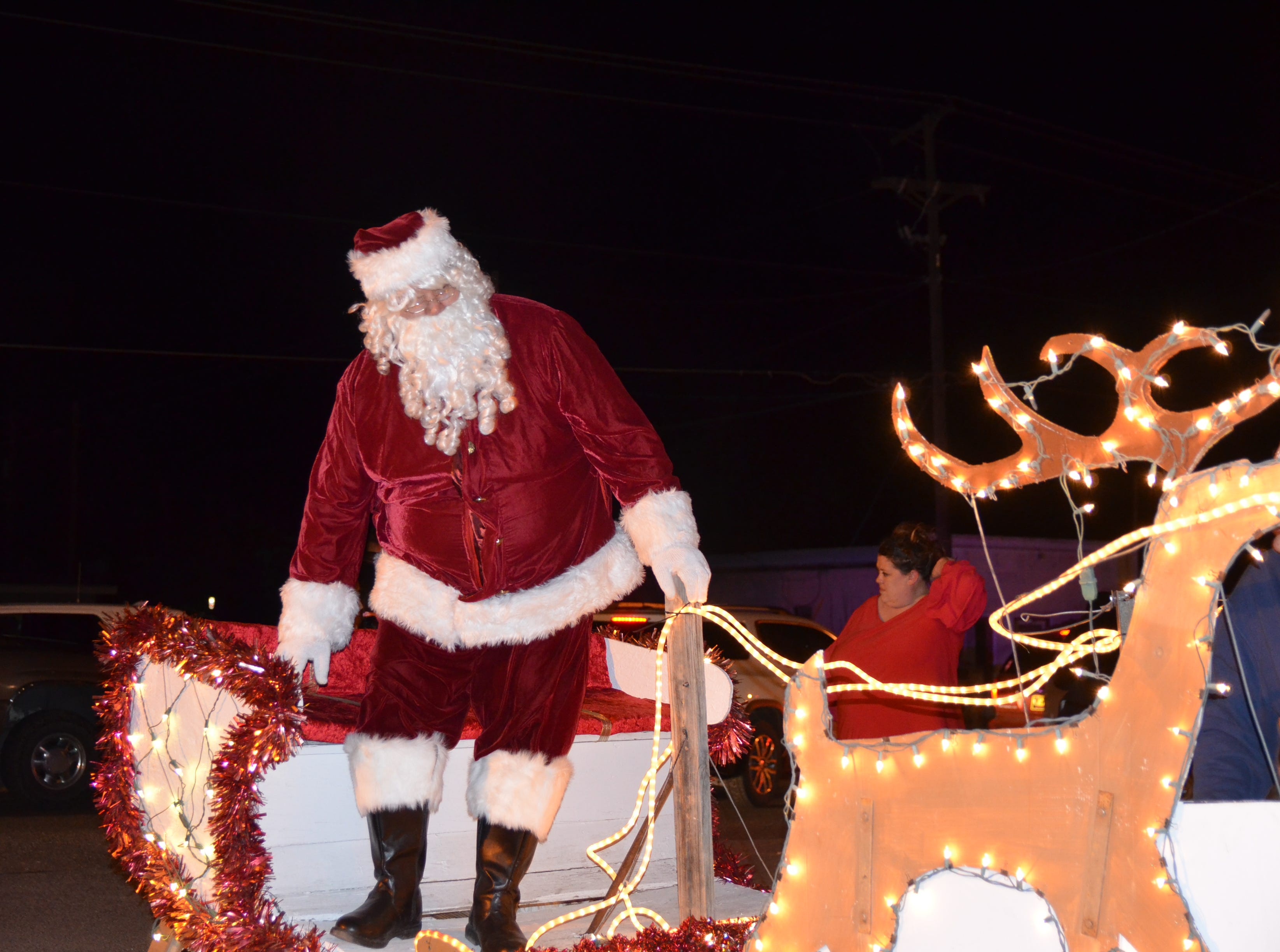 Santa Claus hopping off of his sleigh to meet with Deming Mayor Benny Jasso, County Chair Commissioner Linda Smrkovsky and Deming MainStreet Executive Director Christie Ann Harvey to do the honors of lighting up the Luna County Christmas tree.