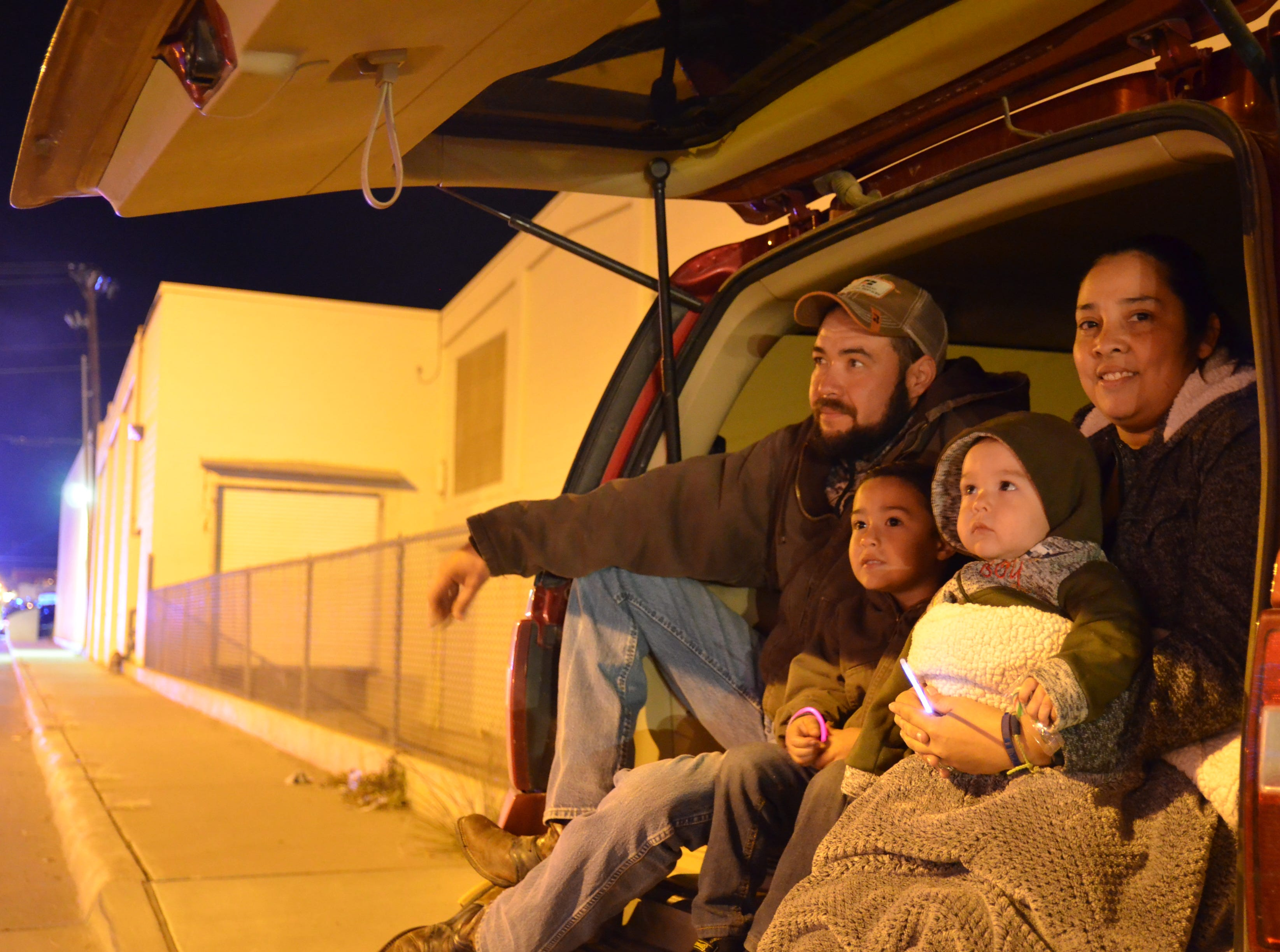 The Piñon family view the lighted Christmas parade from the back of their car.