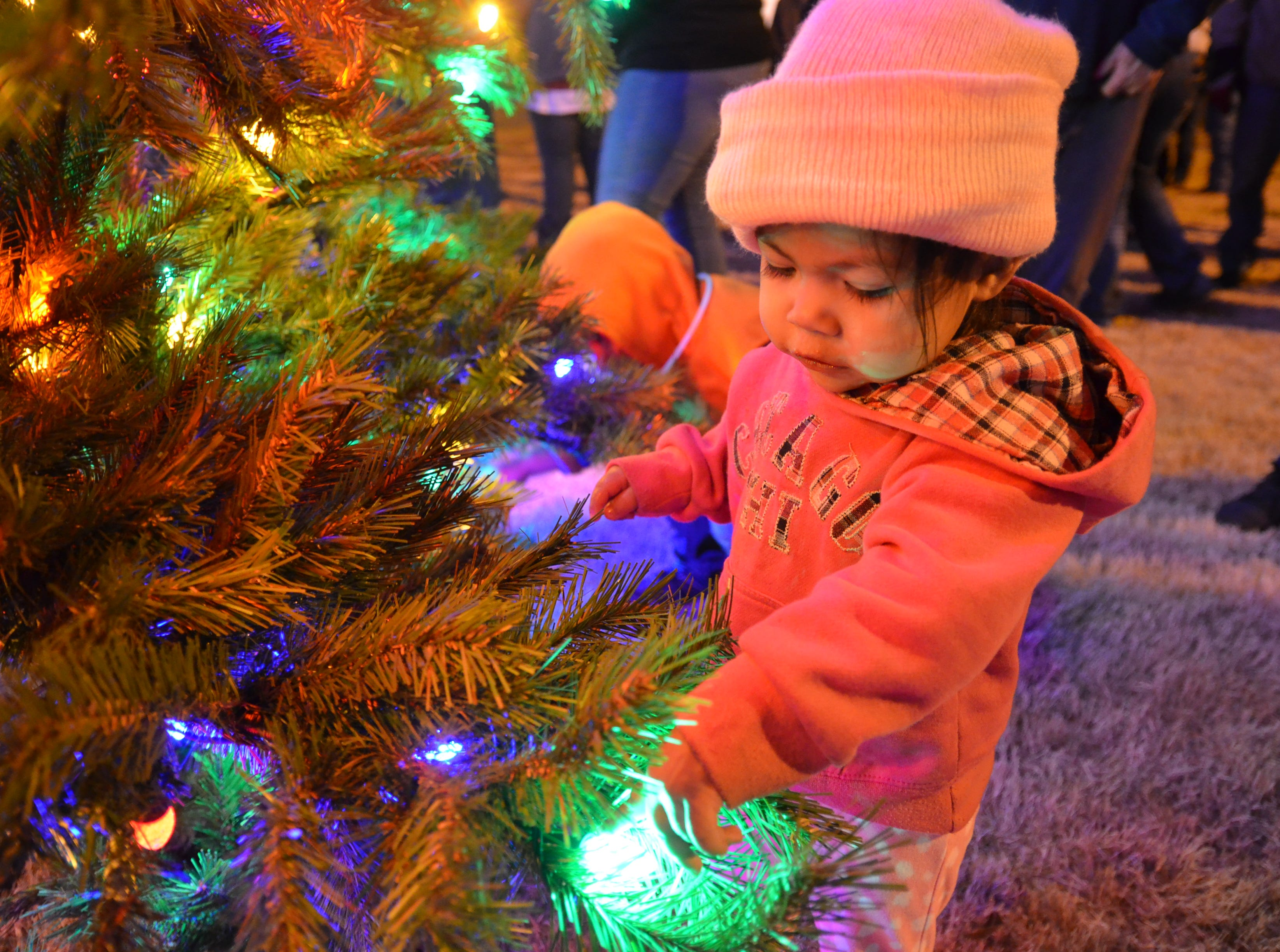 Allie Baca, 1, mesmerized by the beaming lights of Luna County's first ever Christmas tree.