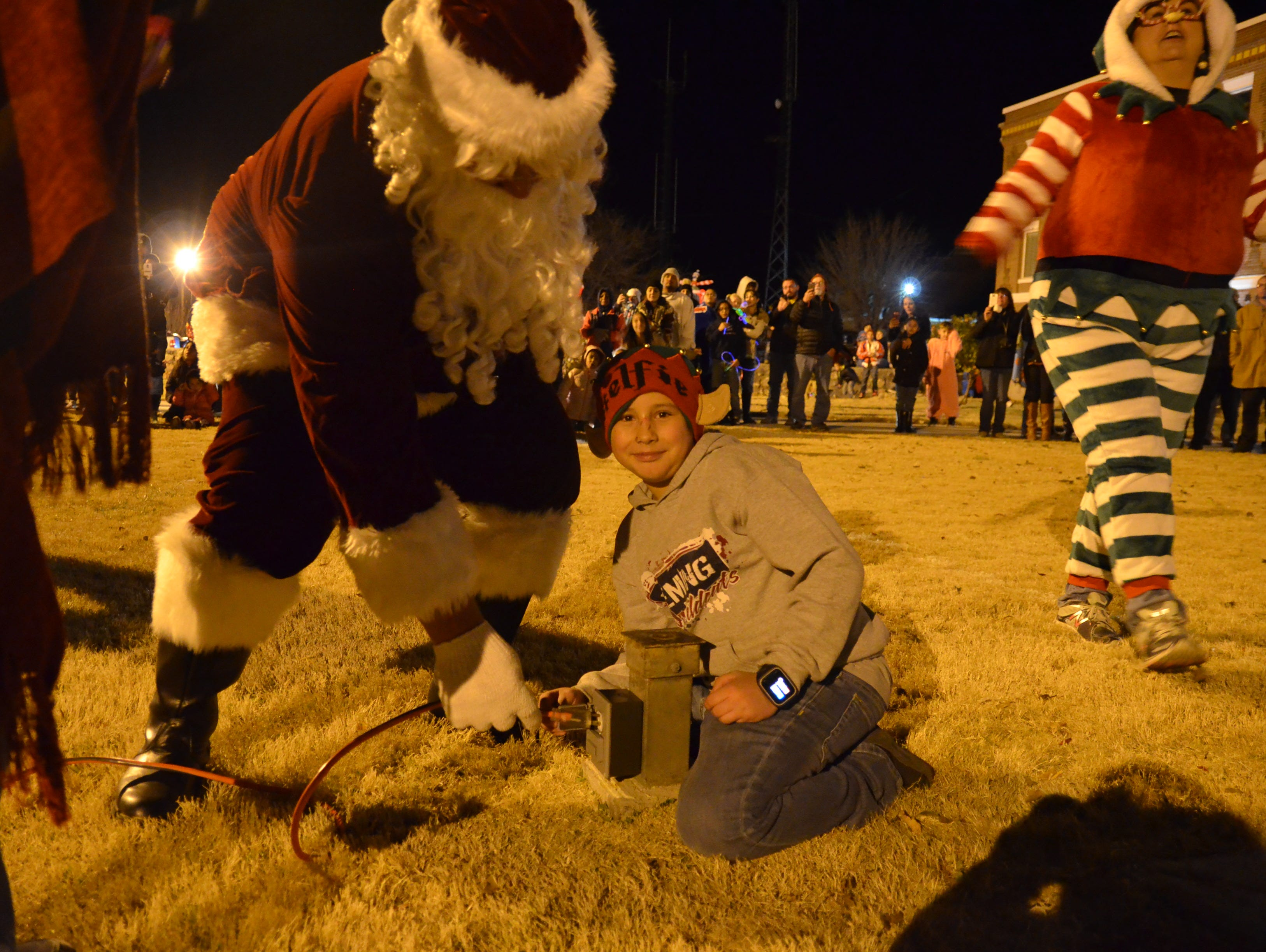 Santa Claus doing the honors of plugging in the cord to light up the Luna County Christmas tree.