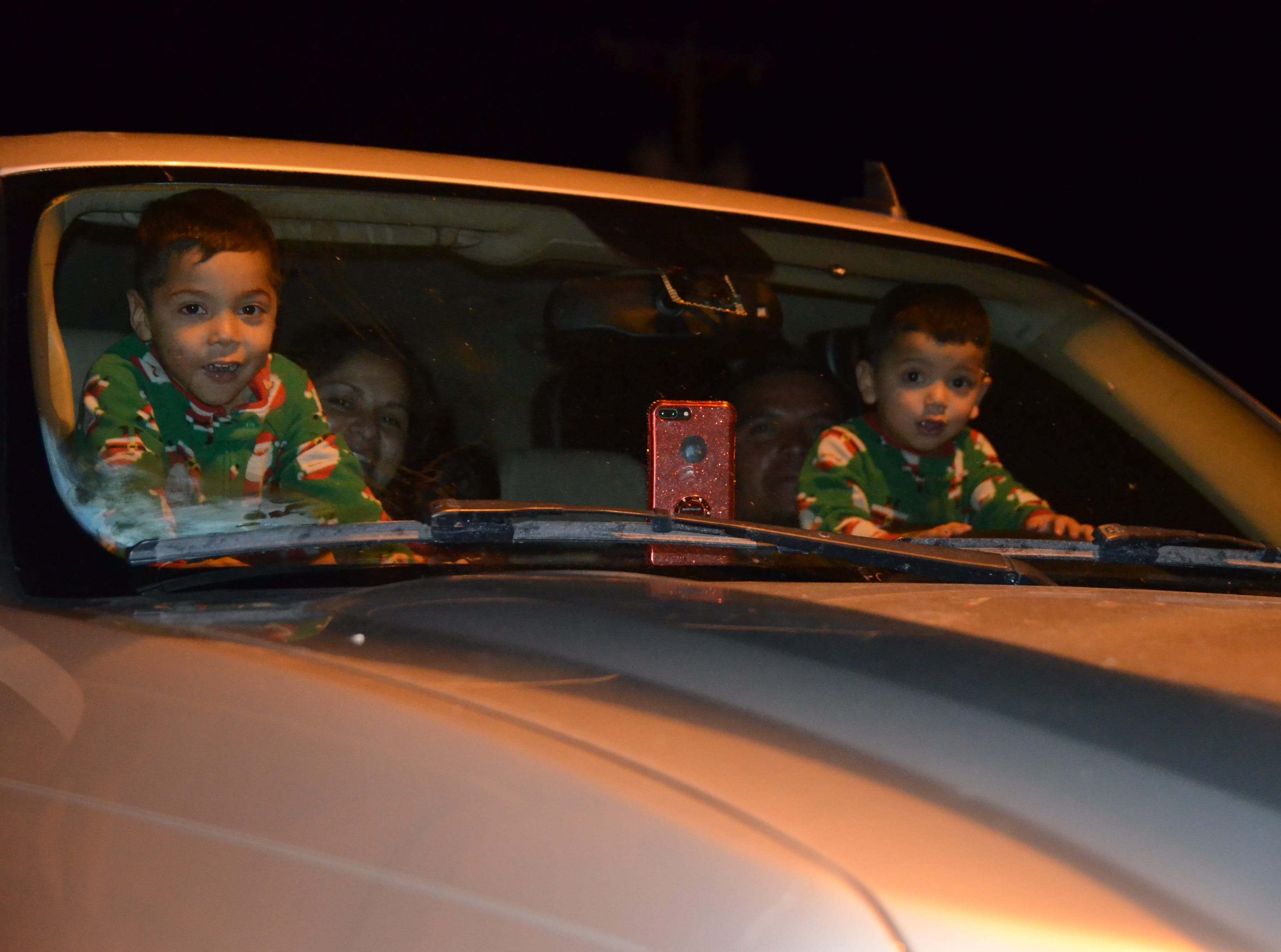 At left, Kevin Bautista, 4, and brother Ivan Bautista, 2, view the lighted Christmas parade from the inside of their family's truck.