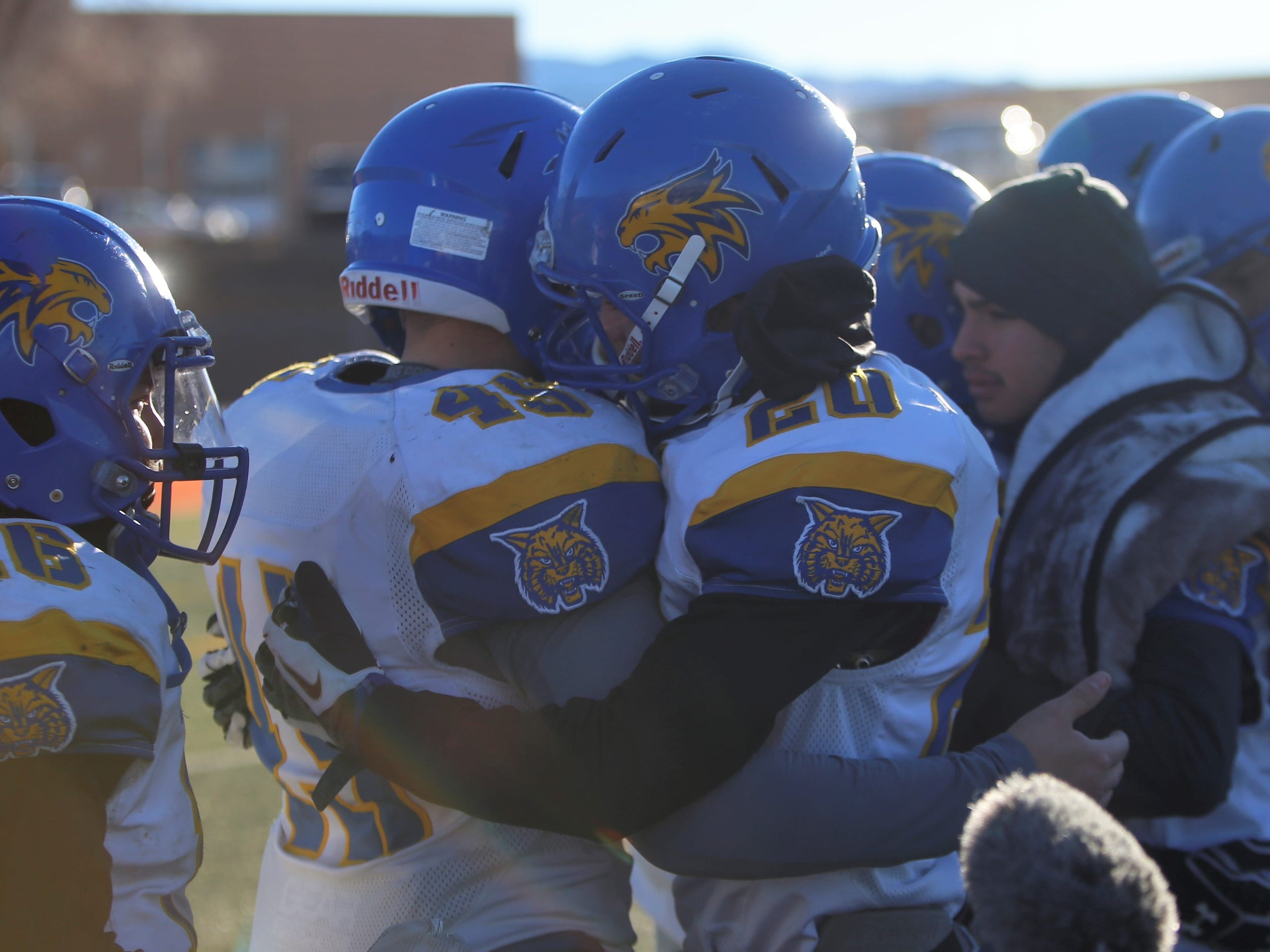Bloomfield's Anthony Gonzales (20) comforts teammate Angelo Atencio (45) following the Bobcats' 14-7 4A state championship game loss Saturday at Taos. BHS made the state finals for the first time since 1990.