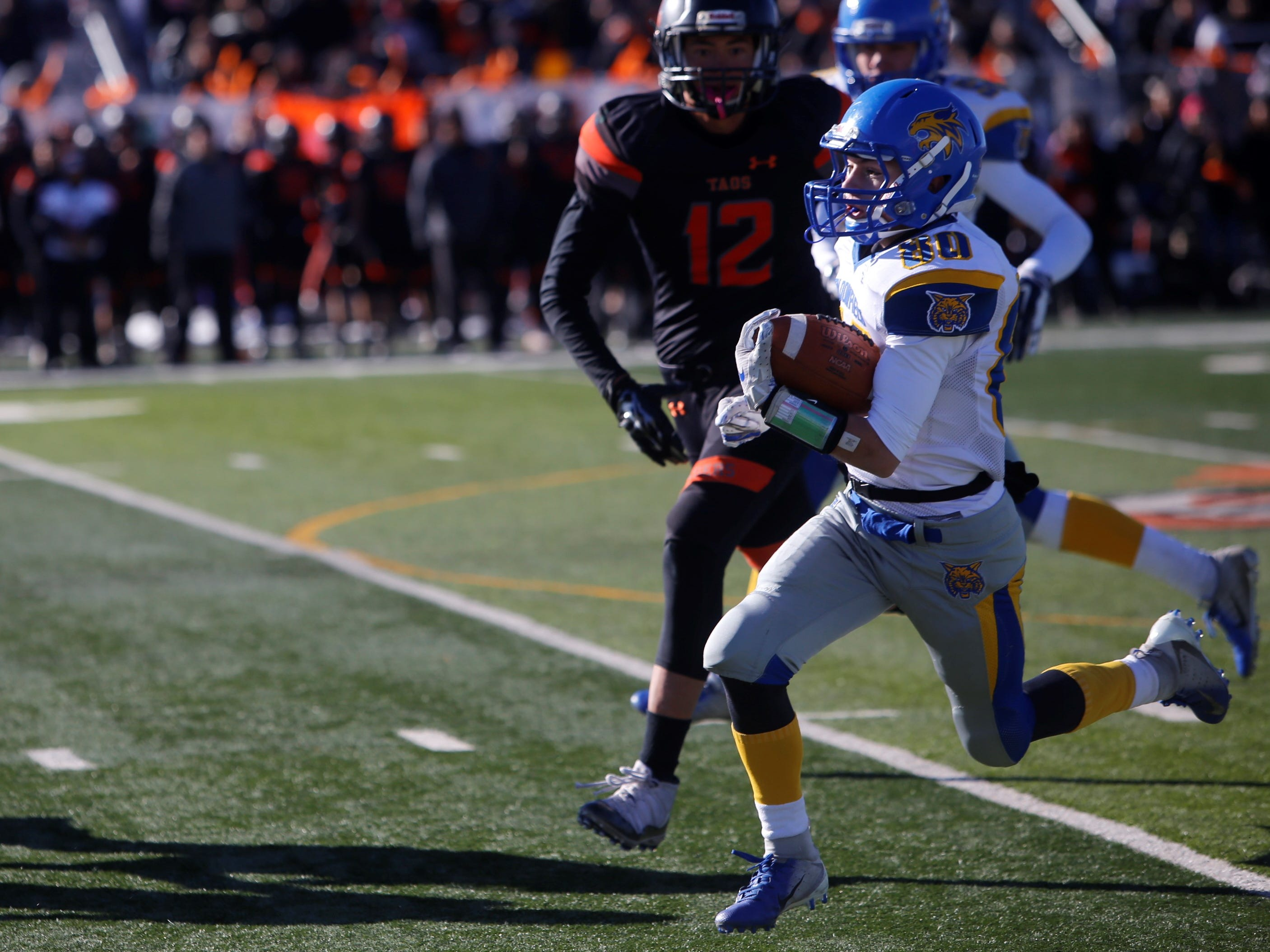 Bloomfield's Tomas Gonzales speeds downfield on a punt return against Taos defender Noah Armijo (12) during Saturday's 4A state championship game at Anaya Field in Taos.