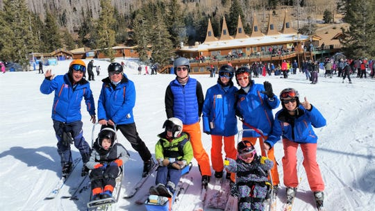 The Patterson family and their coaches gives thumbs up after their ride down the slope in these chairs that are offered to those with physical disabilities to help them experience skiing at the Ski Apache Adaptive Ski Program.