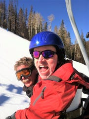 Climbing the mountain on a lift with his coach, this young man that is participating in the Ski Apache Adaptive Ski Program, is excited and ready for his adventure that waits for him.