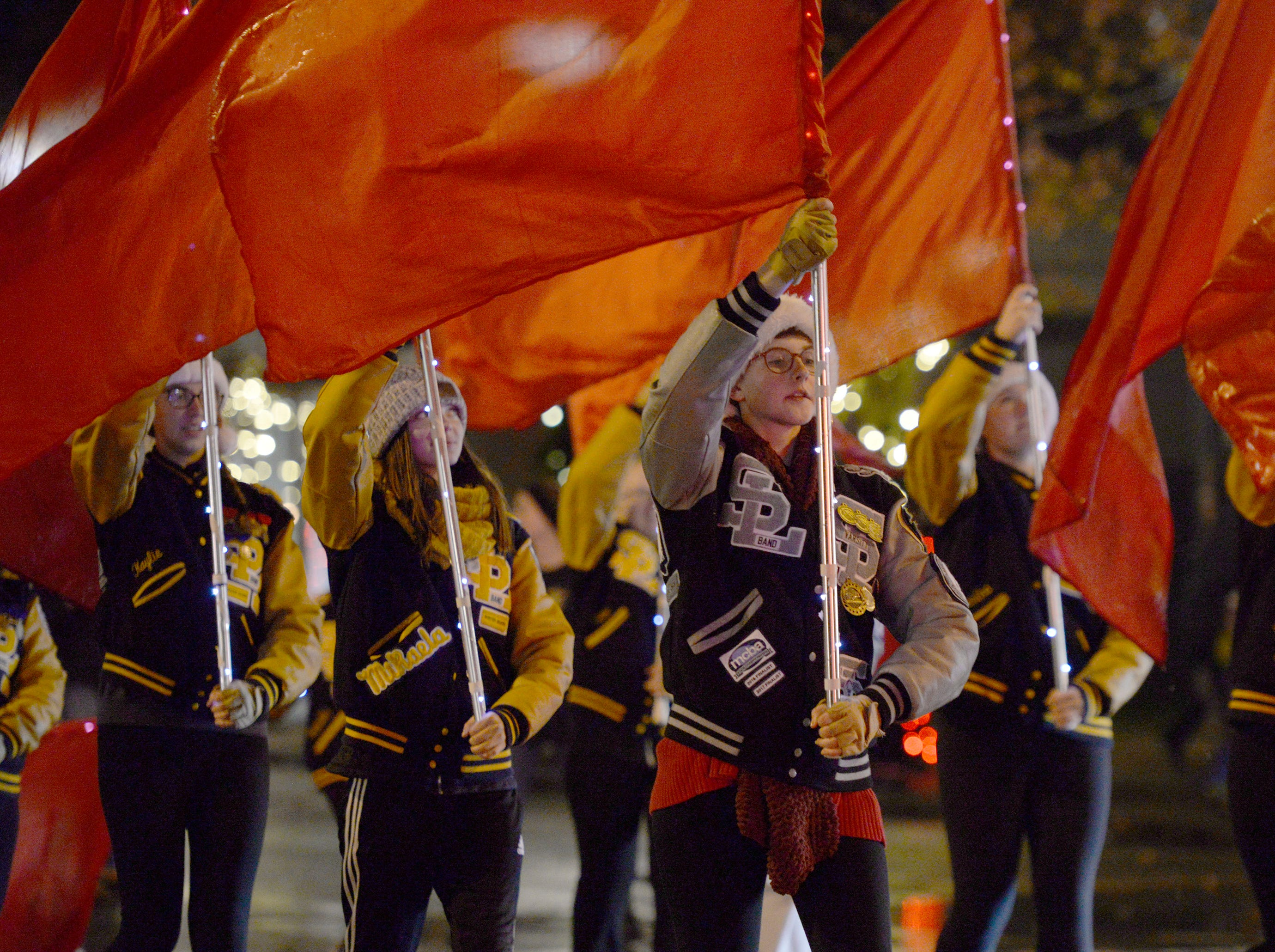 South Lyon High School Marching Band color guard perform during the Lighted Parade Dec. 1, 2018.