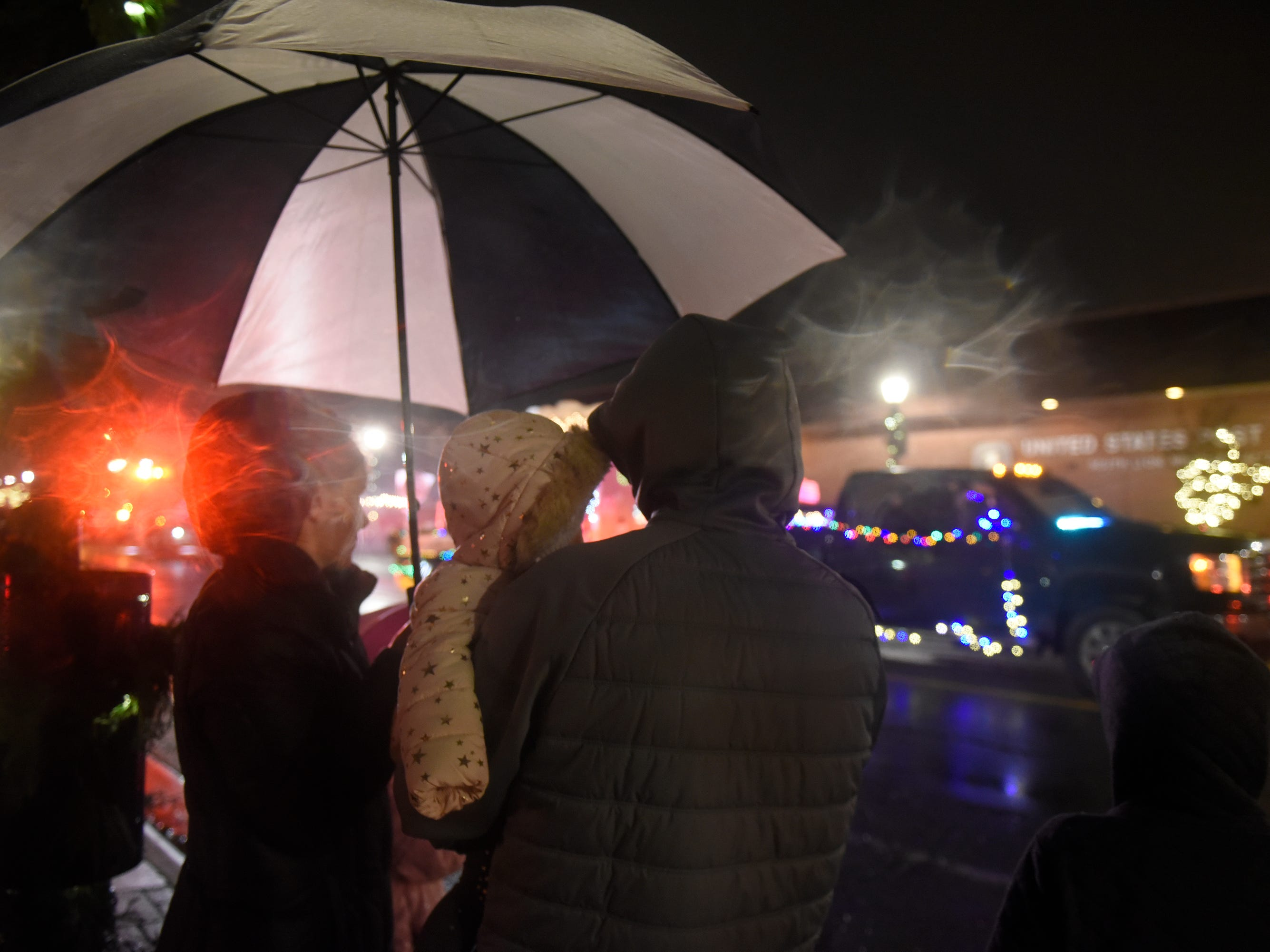 Lighted Parade attendees line Lafayette under umbrellas during South Lyon's Cool Yule celebration Dec. 1, 2018.