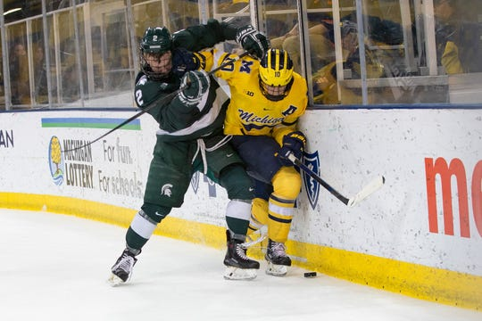 Michigan State defenseman Zach Osburn, of Plymouth, checks Michigan forward Will Lockwood (Bloomfield Hills) during Saturday's Big Ten men's hockey tilt at Yost Ice Arena.