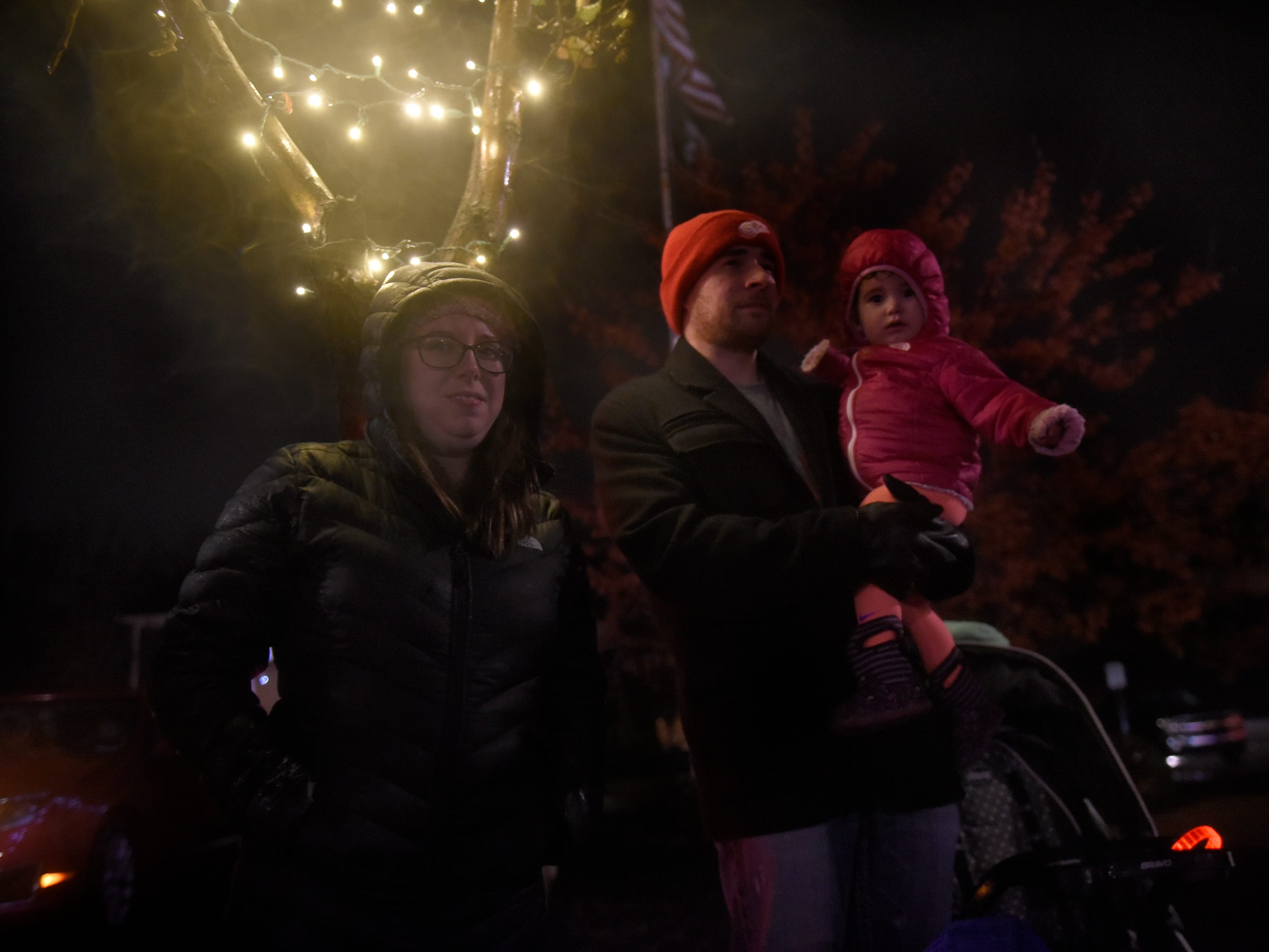 The Echlin family - Jessica (left), Sean and Amylia, 17 months, watch the Lighted Parade during South Lyon's Cool Yule celebration Dec. 1, 2018.