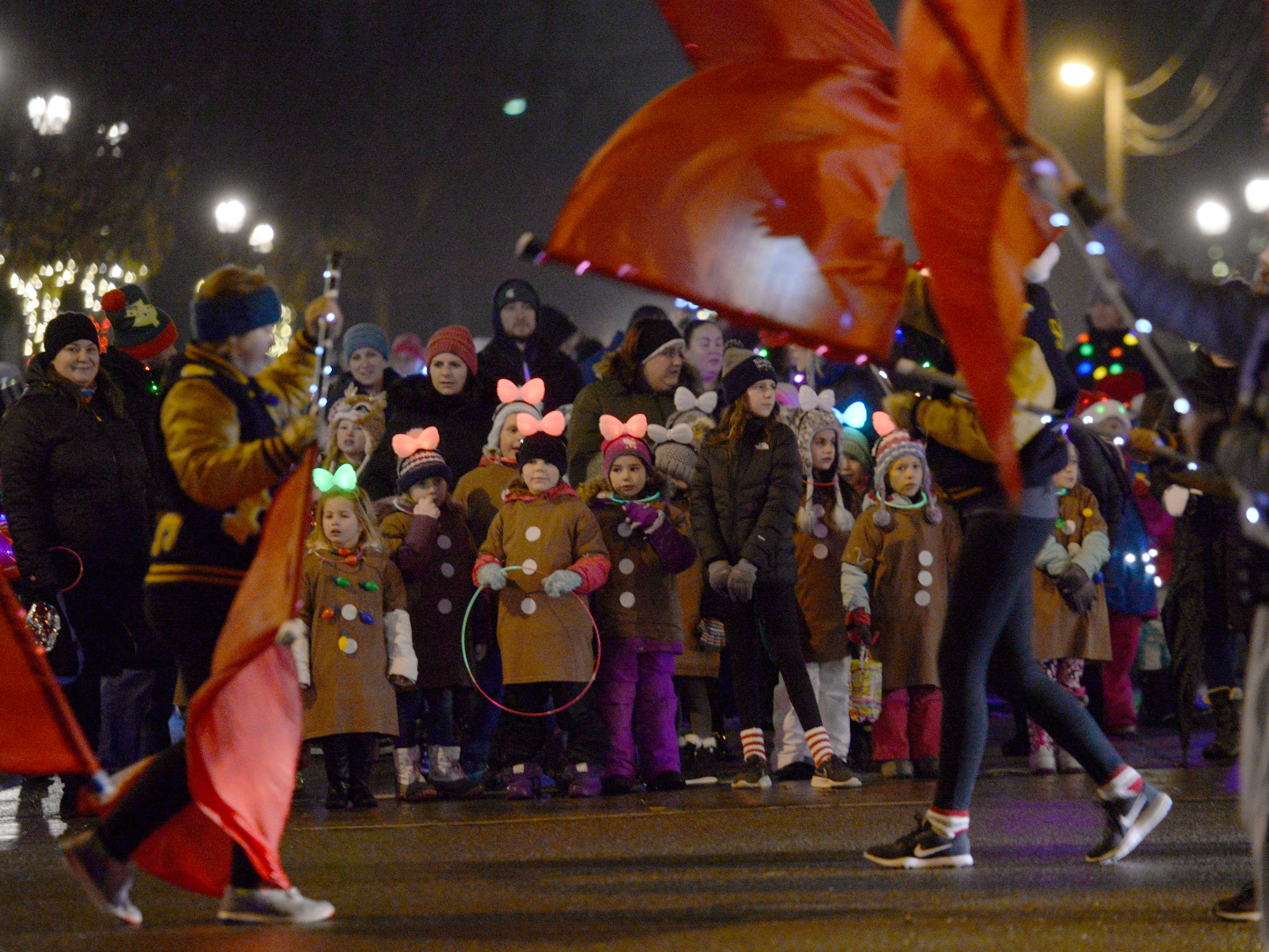 Girl Scouts marching in the Lighted Parade pause at Lafayette and Lake Street while the SLHS color guard performs.