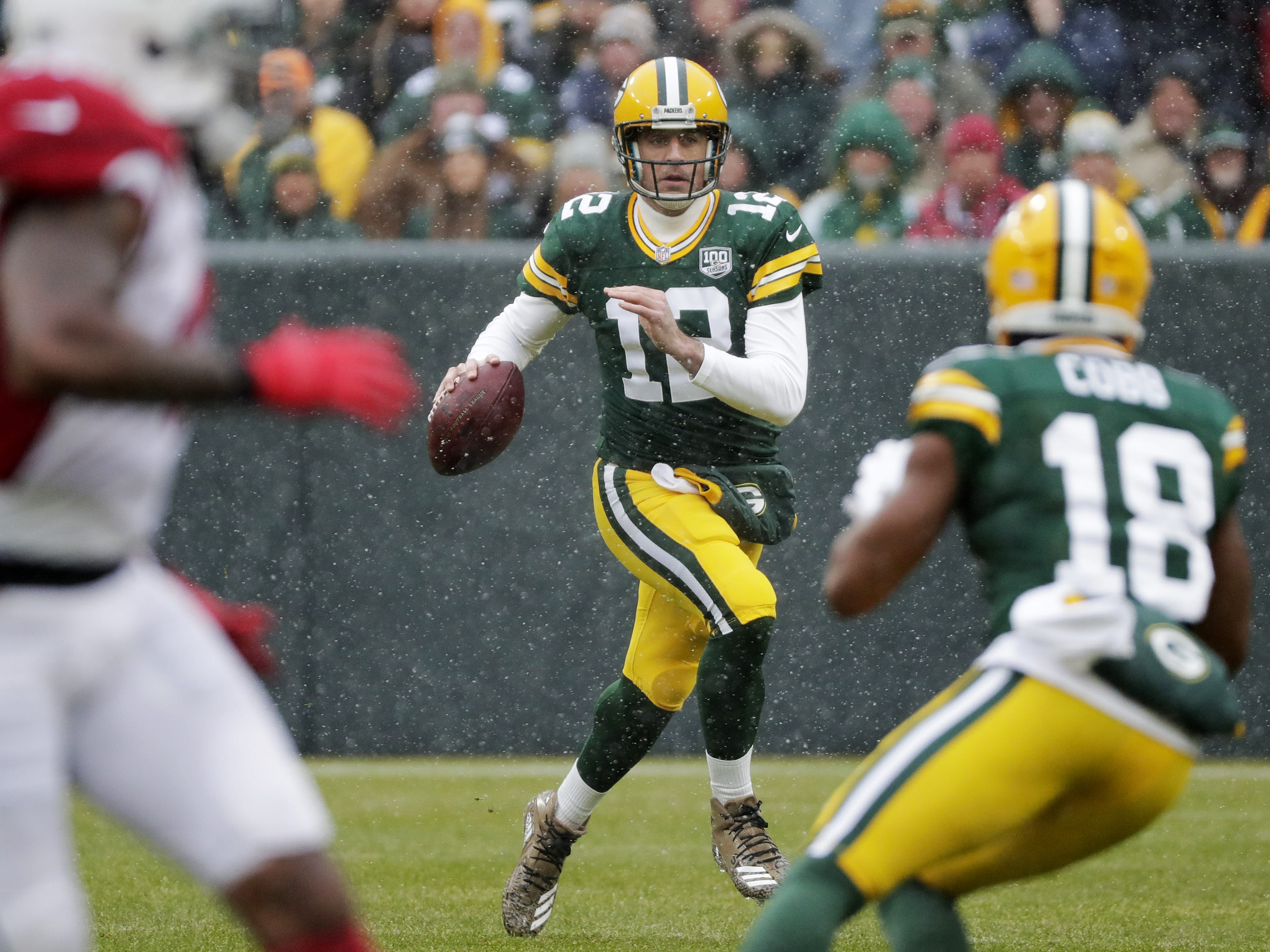 Green Bay Packers quarterback Aaron Rodgers (12) scrambles for a first down against the Arizona Cardinals in the first quarter at Lambeau Field on Sunday, December 2, 2018 in Green Bay, Wis.