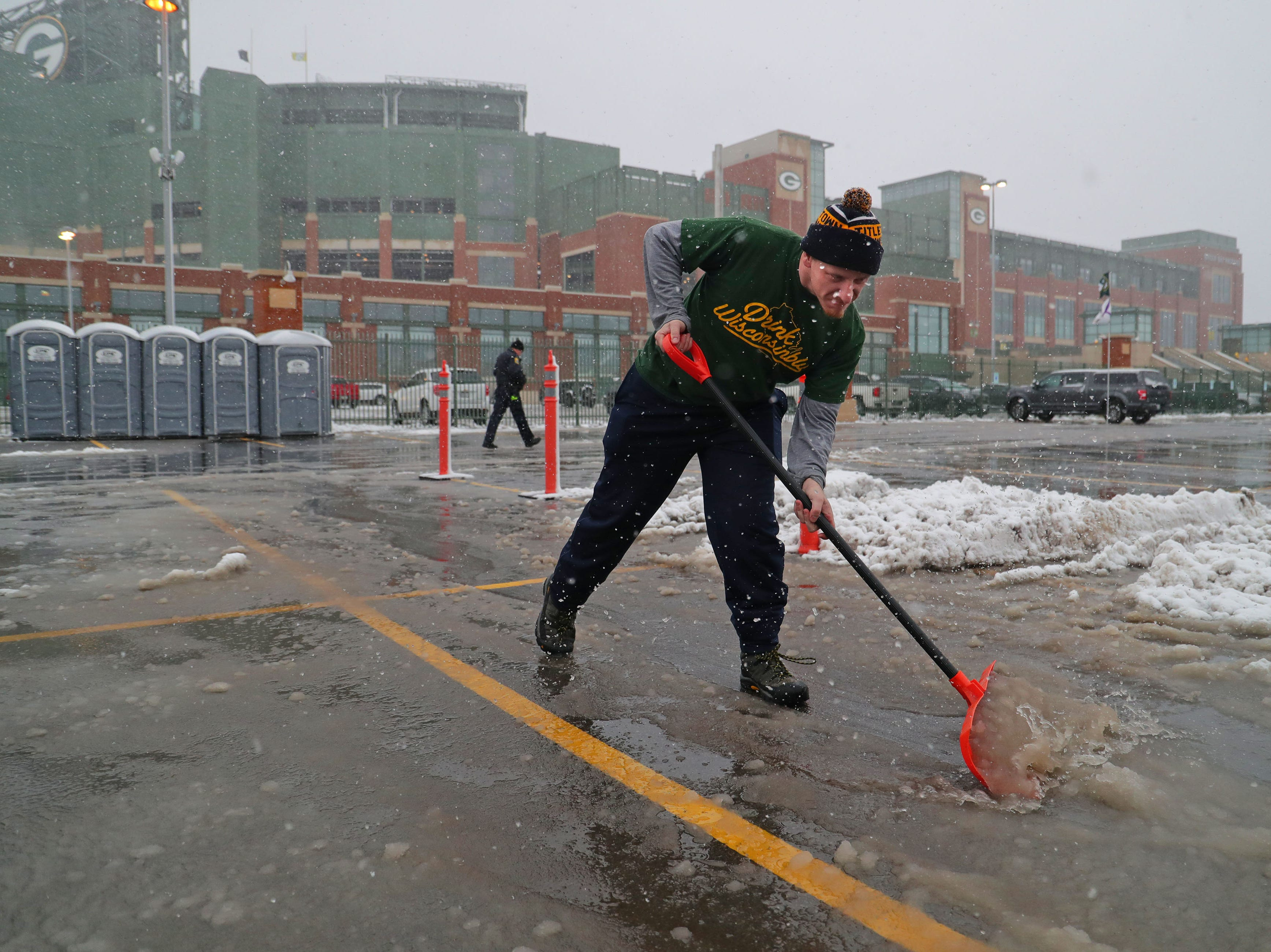 Robert Clarksen, from St. Paul Minn., shovels the snow and slugs from his parking space while tailgating before the Green Bay Packers game against the Arizona Cardinals at Lambeau Field in Green Bay, Wis. on Sunday, December 2, 2018.