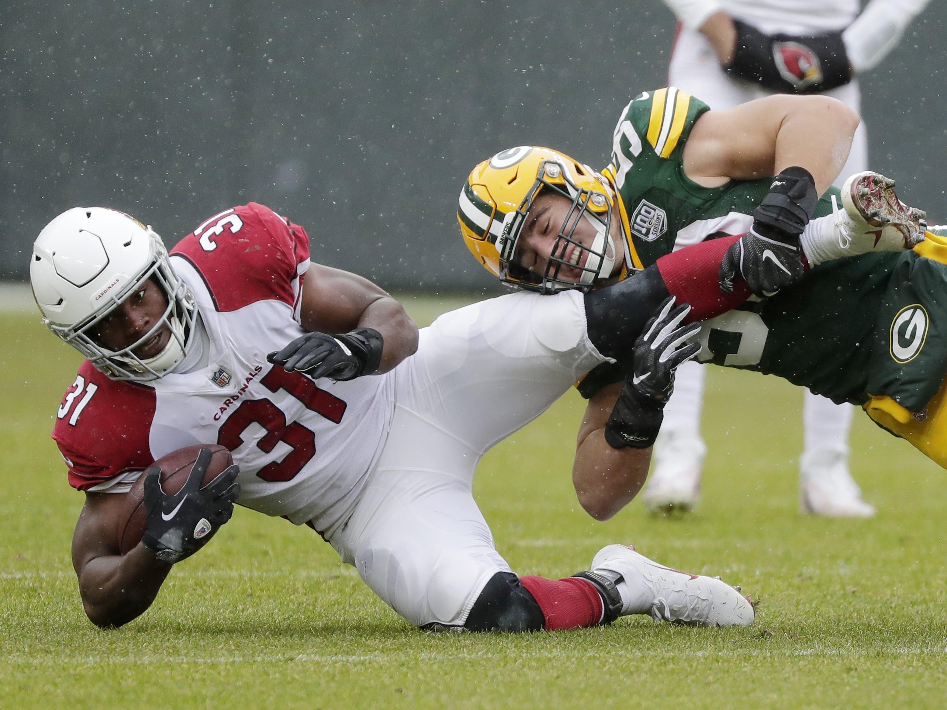 Green Bay Packers linebacker Blake Martinez (50) tackles Arizona Cardinals running back David Johnson (31) in the first quarter at Lambeau Field on Sunday, December 2, 2018 in Green Bay, Wis.