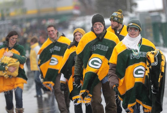 Fans brave cold and wet conditions as they head to the stadium before the Green Bay Packers take on the Arizona Cardinals during their football game on Sunday, December 2, 2018, at Lambeau Field in Green Bay, Wis.