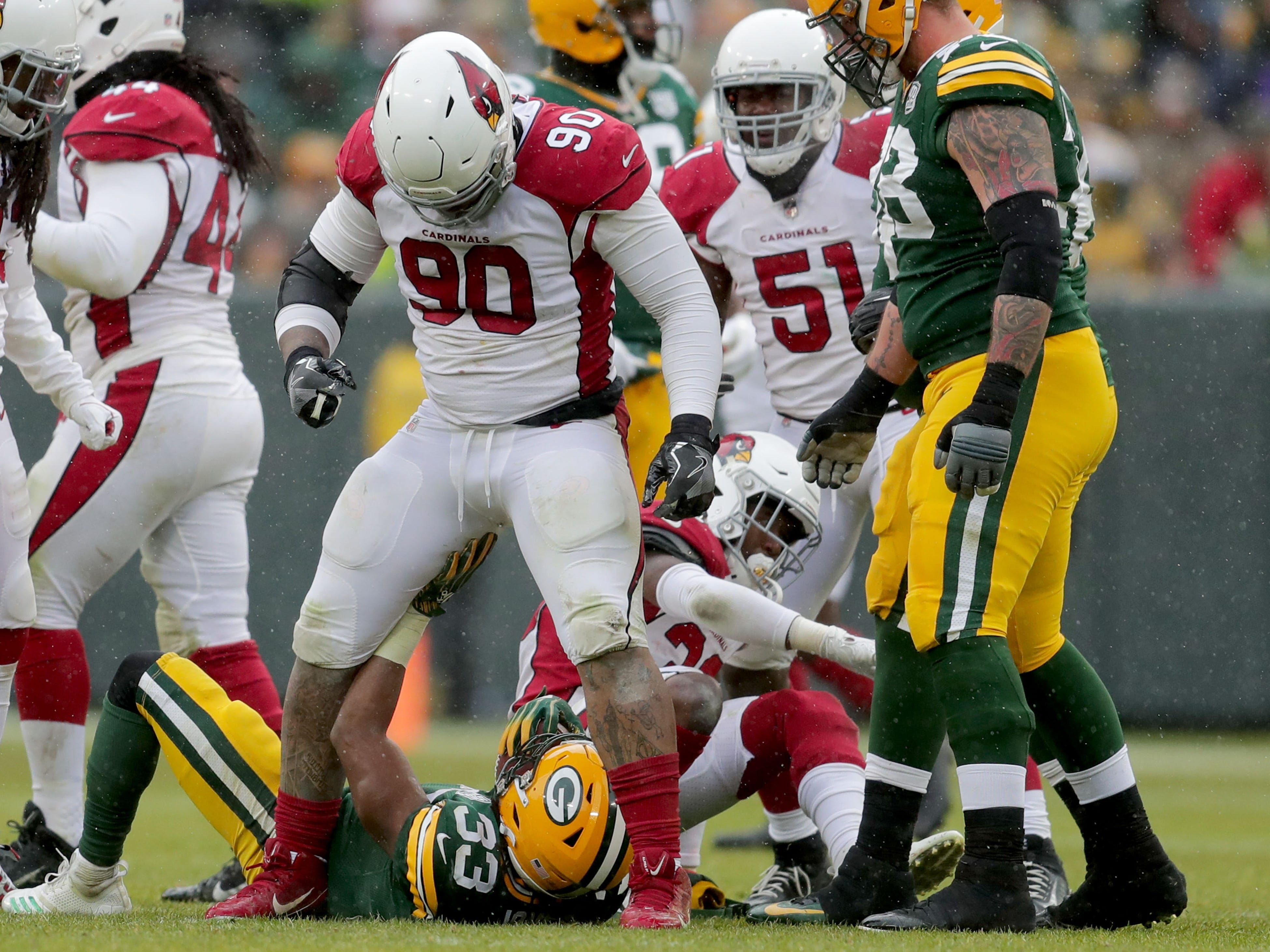 Arizona Cardinals defensive tackle Robert Nkemdiche (90) stands over Green Bay Packers running back Aaron Jones (33) during the 3rd quarter of Green Bay Packers game 20-17 loss against the Arizona Cardinals on Sunday, December 2, 2018 at Lambeau Field in Green Bay, Wis. Mike De Sisti / USA TODAY NETWORK-Wis
