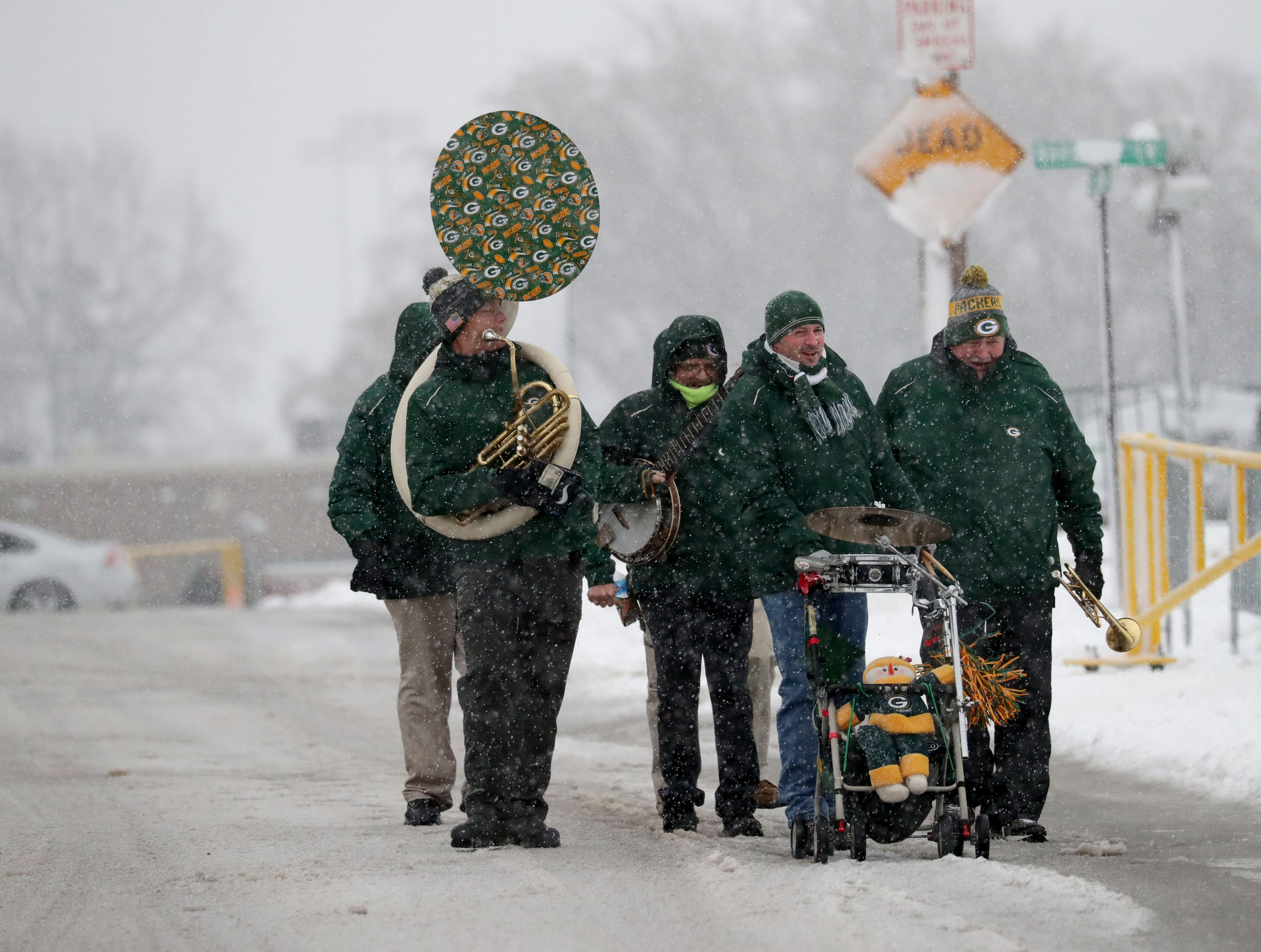 The Packers Tailgate Band makes their way through the snow before playing for tailgaters before the Green Bay Packers game against the Arizona Cardinals at Lambeau Field in Green Bay, Wis. on Sunday, December 2, 2018.