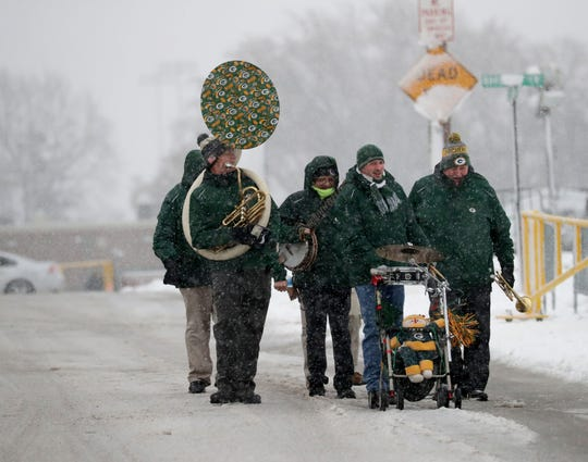 The Packers Tailgate Band makes its way through the snow before playing for tailgaters before the Green Bay Packers game against the Arizona Cardinals at Lambeau Field in Green Bay on  Dec. 2, 2018.