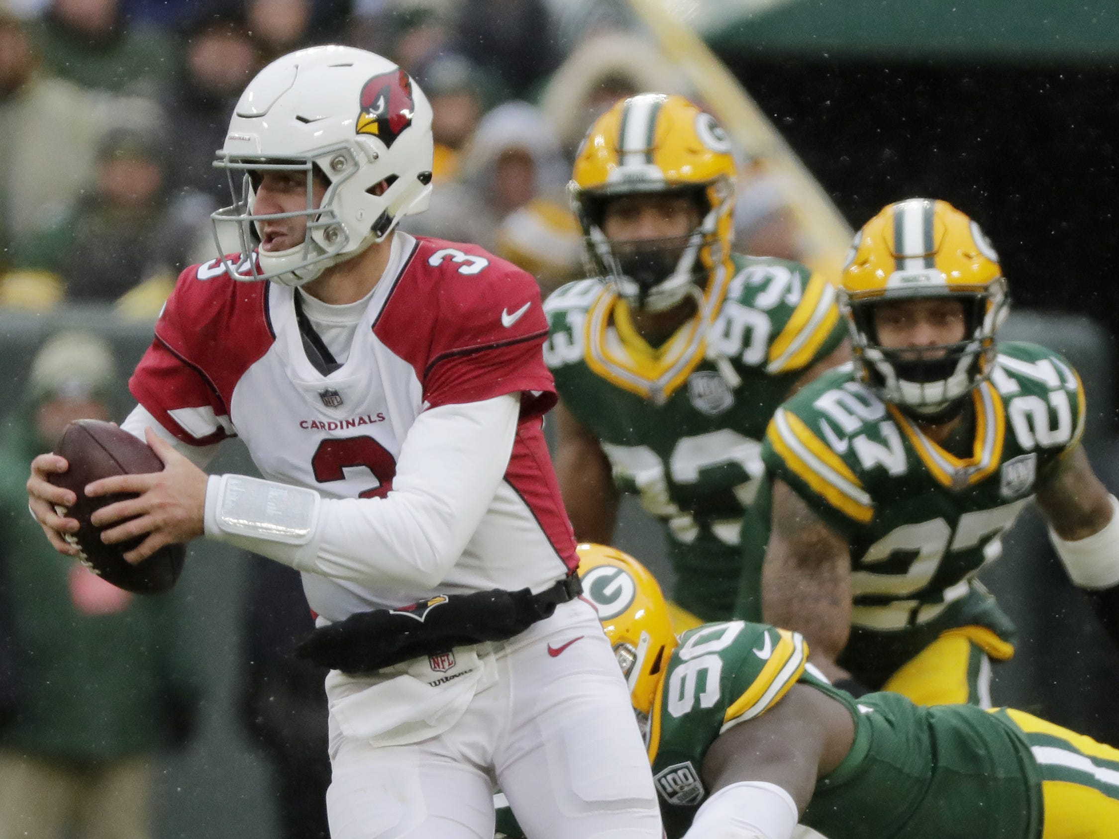 Arizona Cardinals quarterback Josh Rosen (3) escapes pressure by Green Bay Packers defensive tackle Montravius Adams (90) in the third quarter at Lambeau Field on Sunday, December 2, 2018 in Green Bay, Wis.