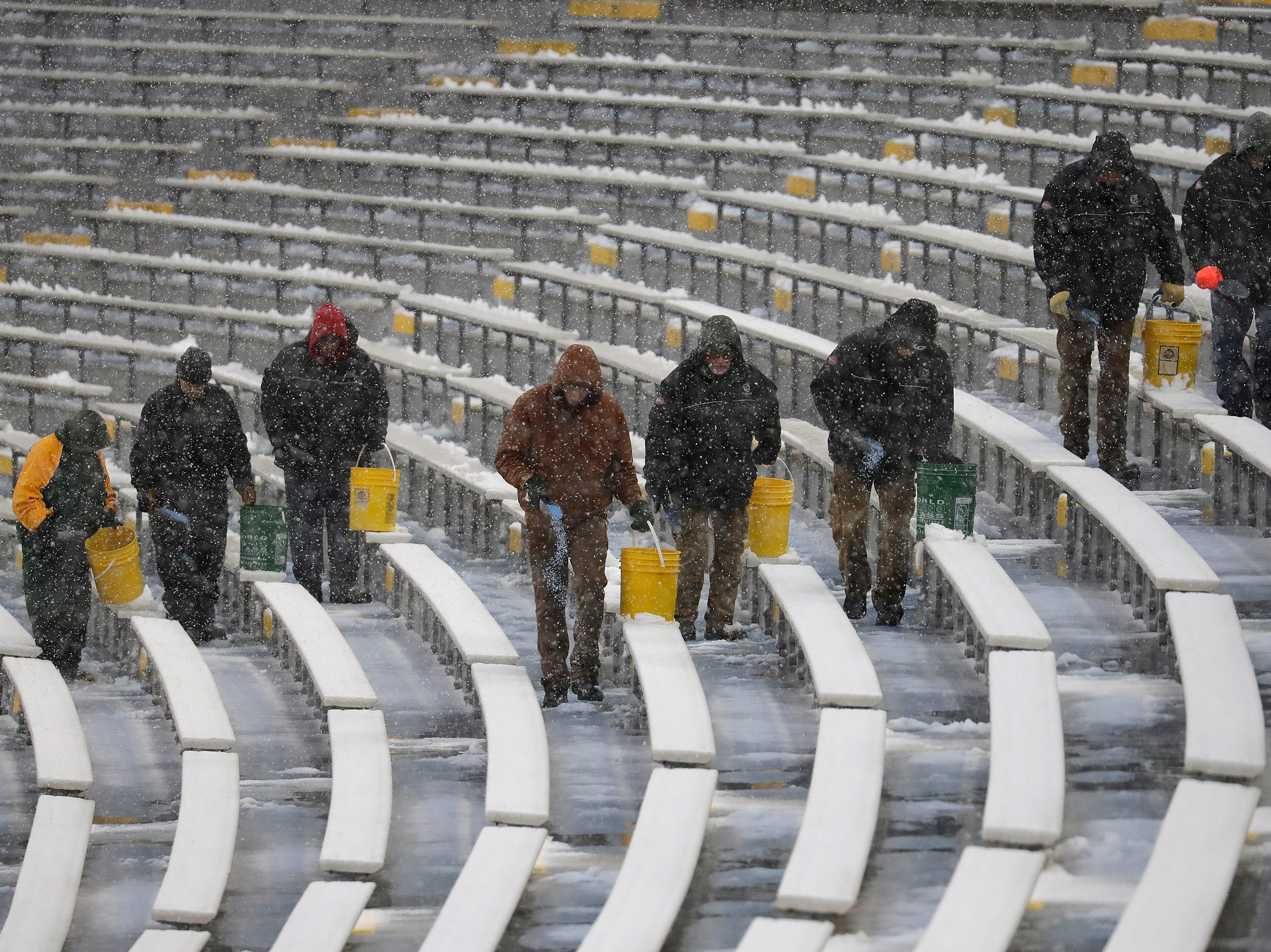 Workers spread salt in the seating area before the Green Bay Packers play against the Arizona Cardinals Sunday, December 2, 2018, at Lambeau Field in Green Bay, Wis.