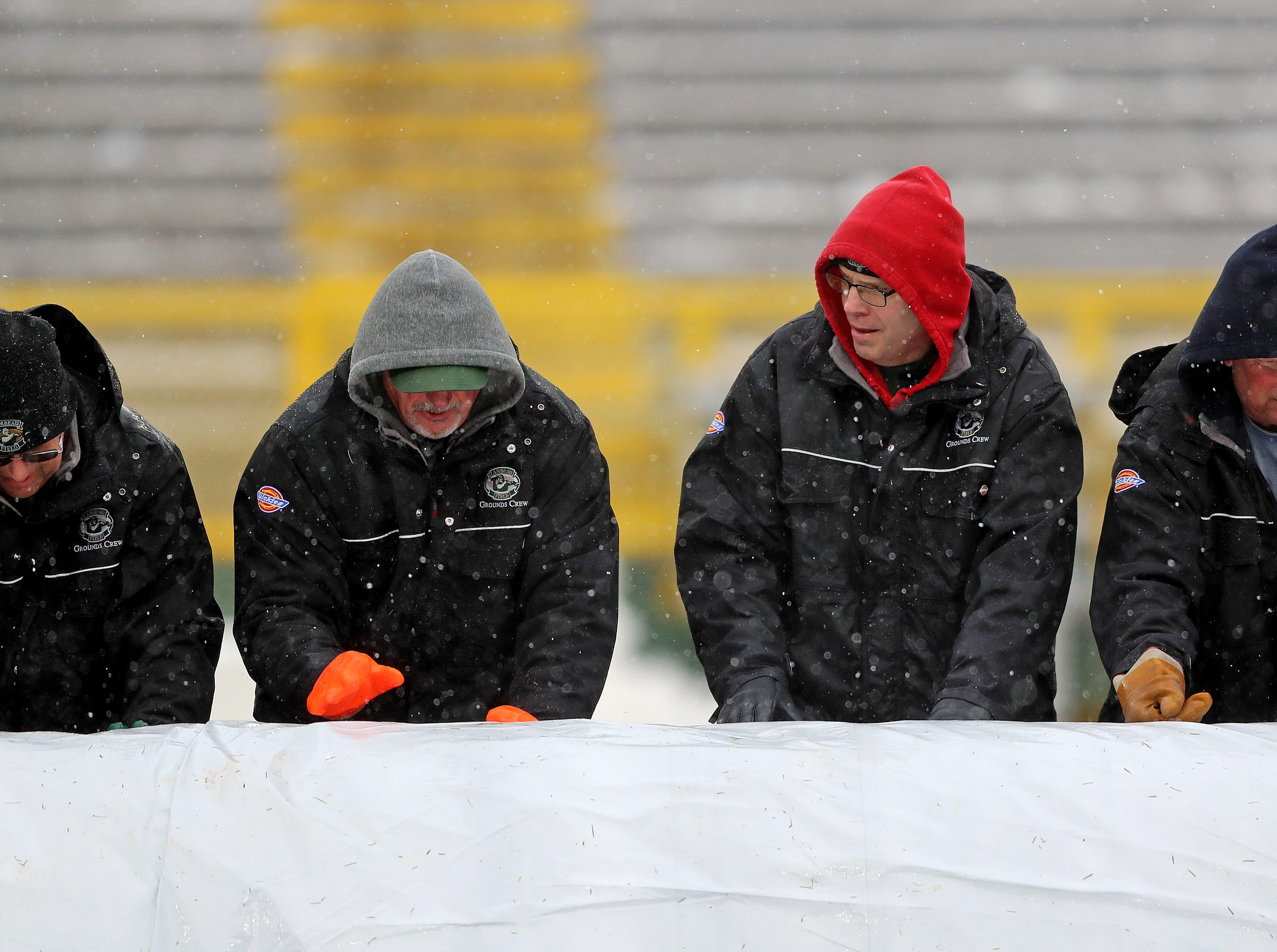 The Lambeau Field stadium crew roll the wet tarp off the grassy surface before the game against the Arizona Cardinals Sunday, December 2, 2018 at Lambeau Field in Green Bay, Wis.Jim Matthews/USA TODAY NETWORK-Wis