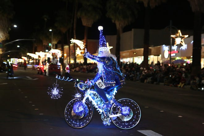 Claudio Dagostino rides a bicycle illuminated in lights during the 26th annual Palm Springs Festival of Lights parade in downtown Palm Springs on Dec. 1, 2018.