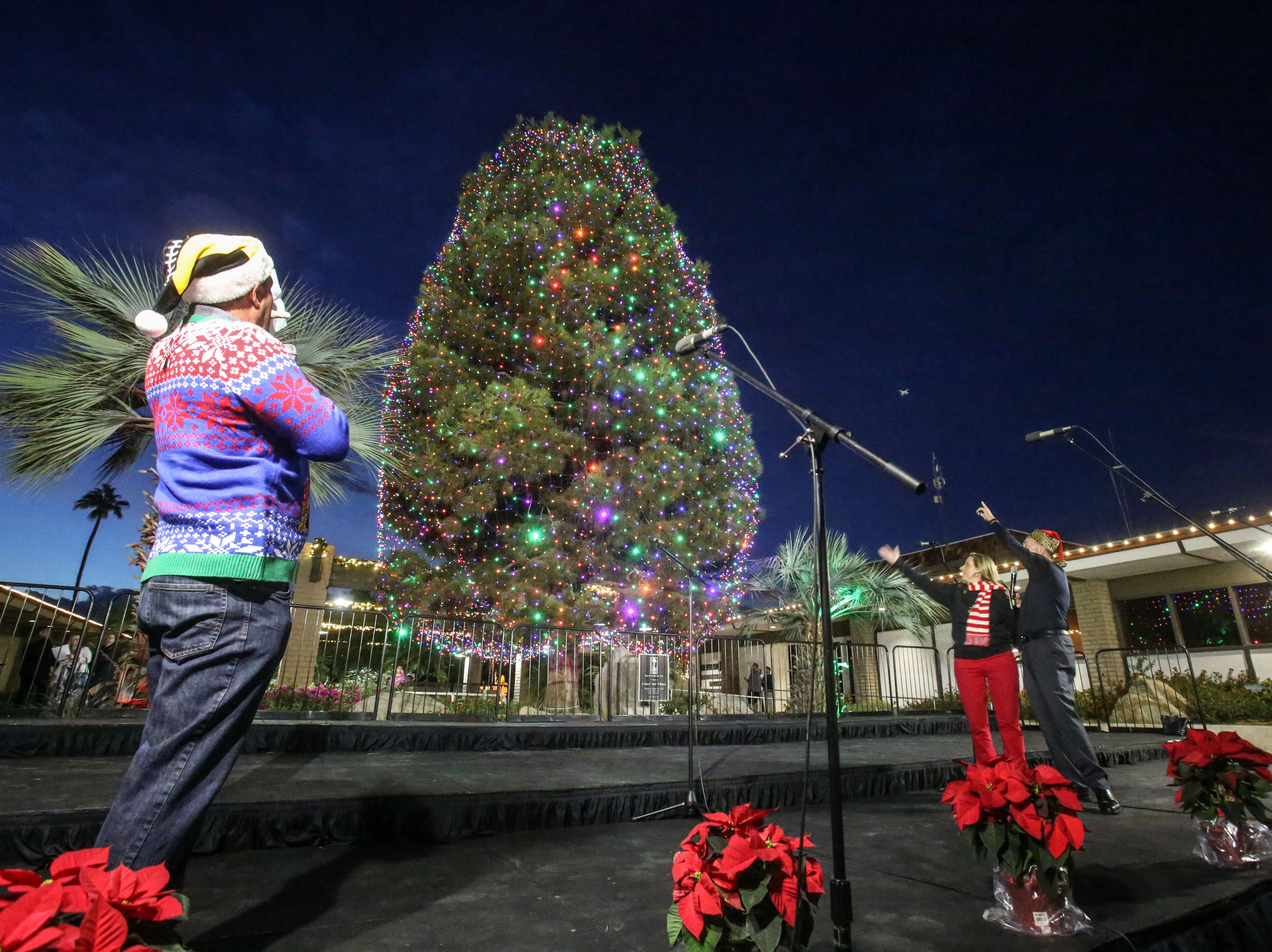 Indio City Council members Glenn Miller and Elaine Holmes initiate the light of the City of Indio's Christmas tree as host Jim Curtis, left, looks on Saturday, December 1, 2018 in Indio.
