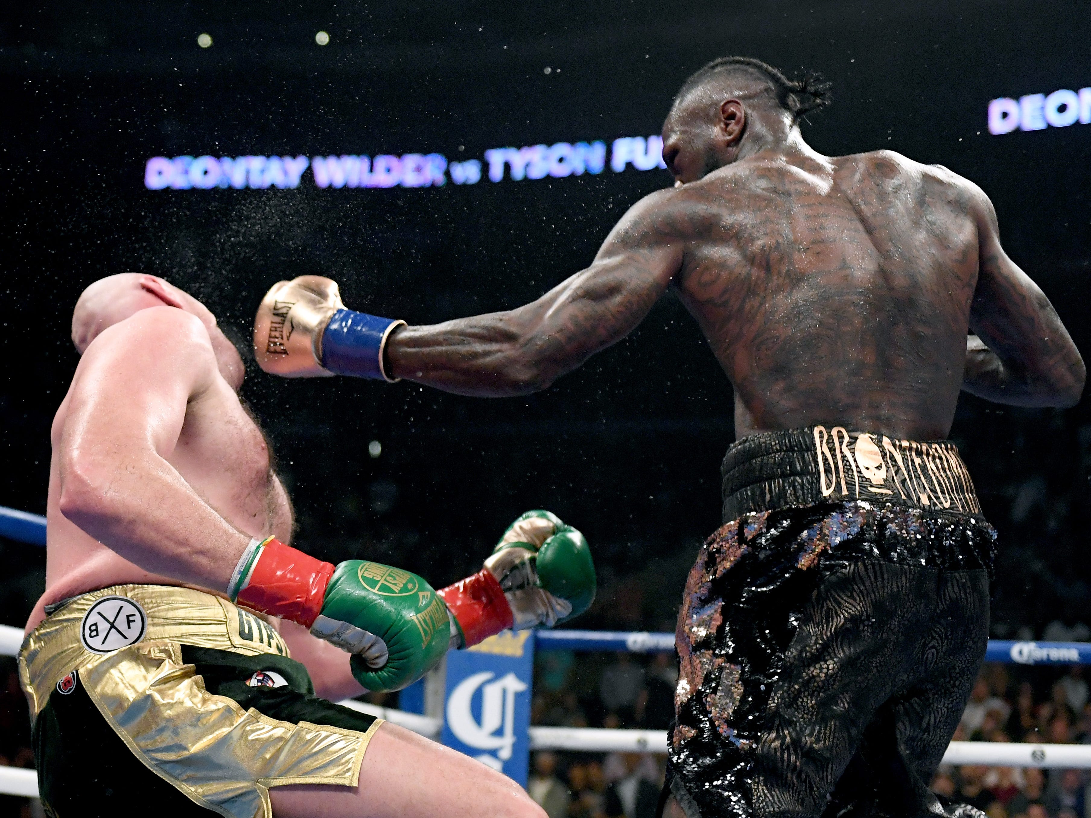 Deontay Wilder knocks Tyson Fury down with a left hand during the 12th round of their WBC heavyweight title fight Dec. 1 at Staples Center.