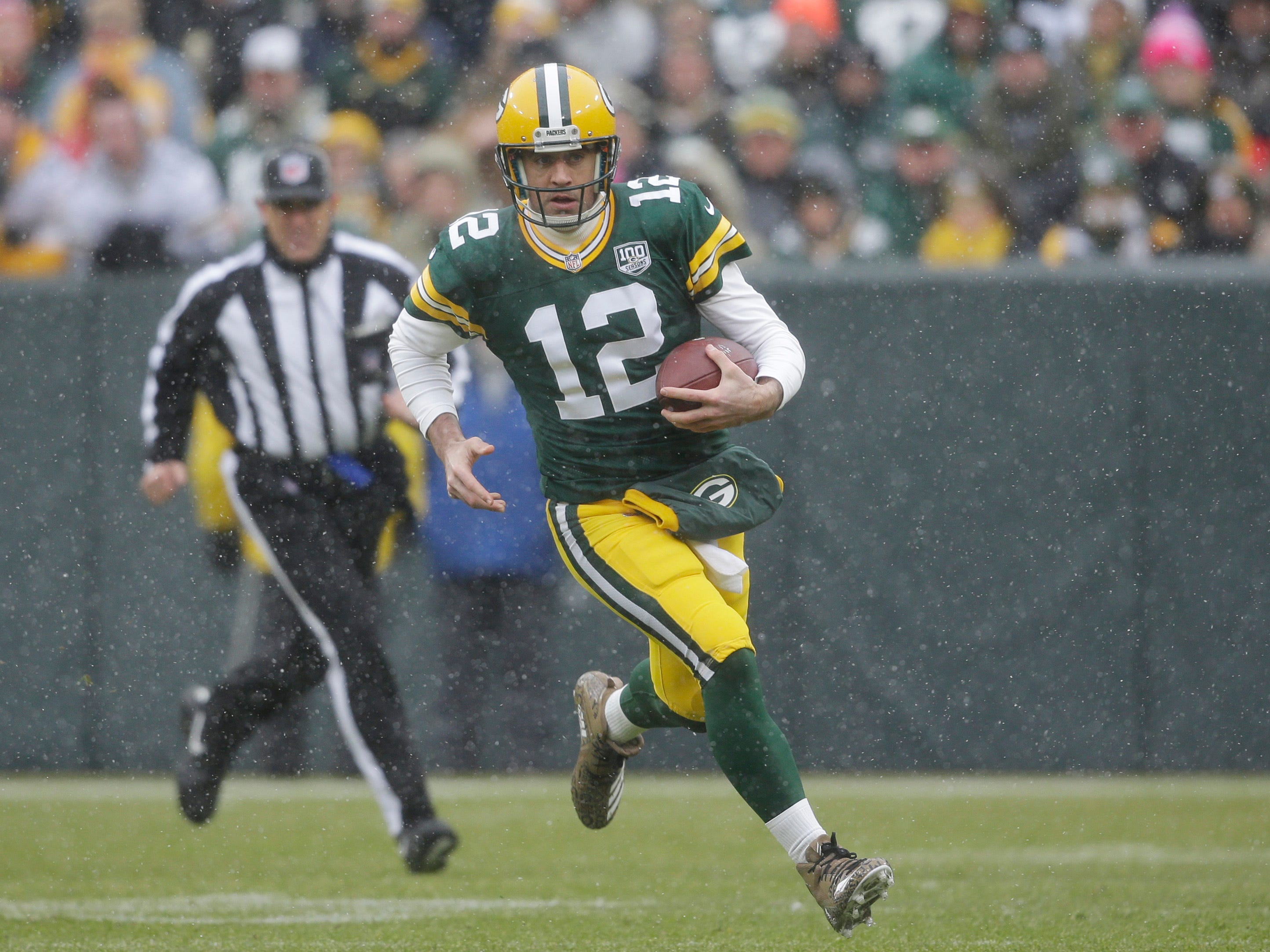 Green Bay Packers quarterback Aaron Rodgers rushes with the ball during the first half of an NFL football game against the Arizona Cardinals Sunday, Dec. 2, 2018, in Green Bay, Wis. (AP Photo/Jeffrey Phelps)
