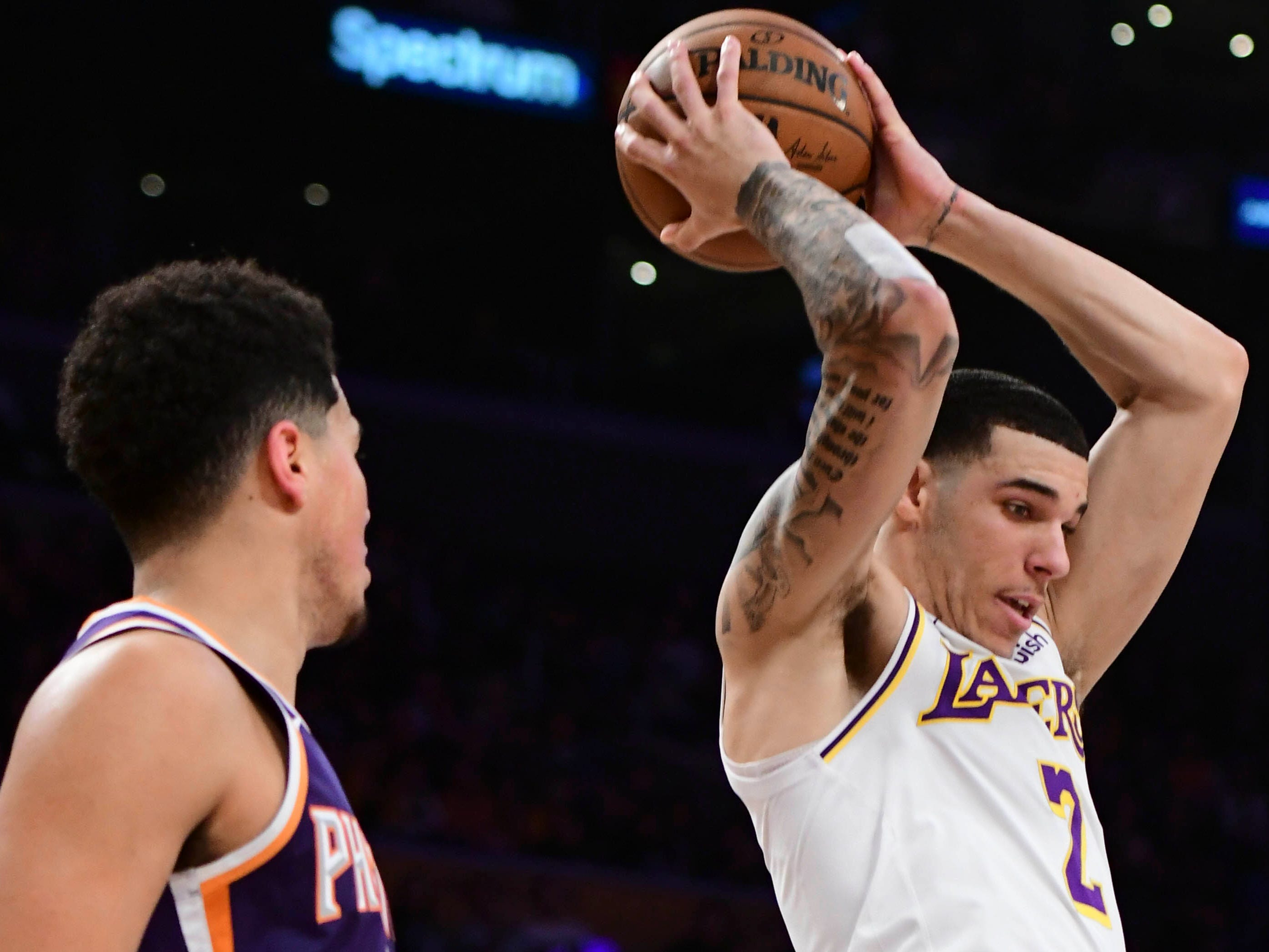 Dec 2, 2018; Los Angeles, CA, USA; Los Angeles Lakers guard Lonzo Ball (2) grabs a rebound in front of Phoenix Suns guard Devin Booker (1) during the second quarter at Staples Center. Mandatory Credit: Robert Hanashiro-USA TODAY Sports