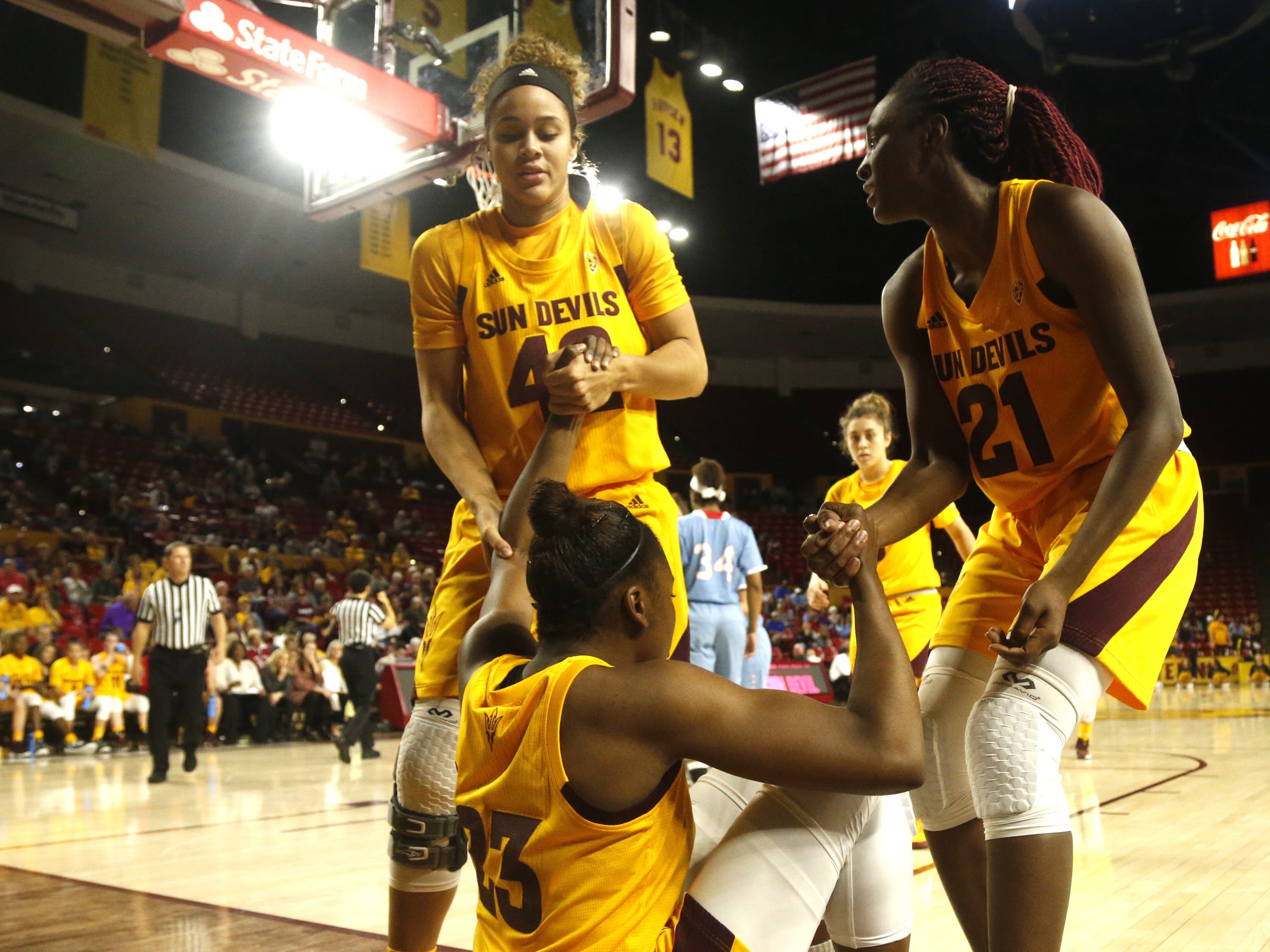 ASU's Kianna Ibis (42) and Sophia Elenga (21) lift Iris Mbulito (23) from the court during the second half at Wells Fargo Arena in Tempe, Ariz. on November 30, 2018.