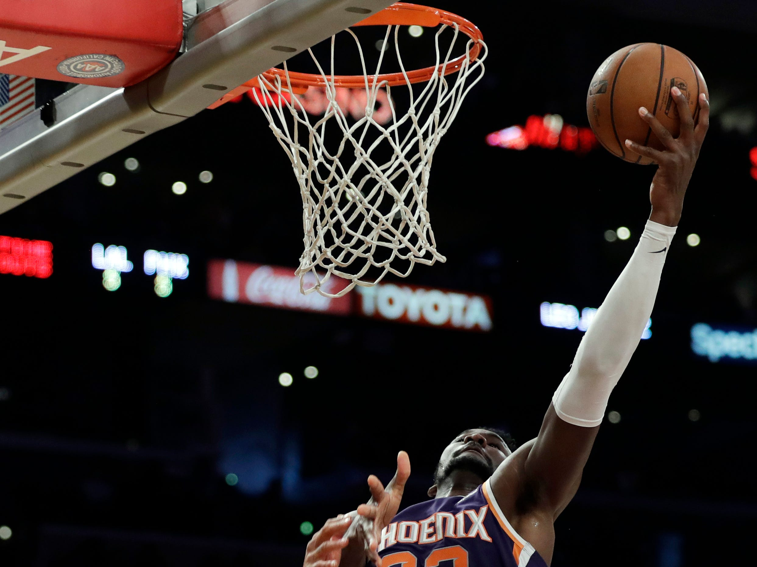 Phoenix Suns' Deandre Ayton (22) drives past Los Angeles Lakers' Brandon Ingram during the first half of an NBA basketball game Sunday, Dec. 2, 2018, in Los Angeles. (AP Photo/Marcio Jose Sanchez)